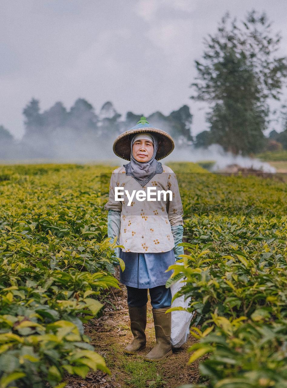 Portrait Of Senior Woman Standing At Farm