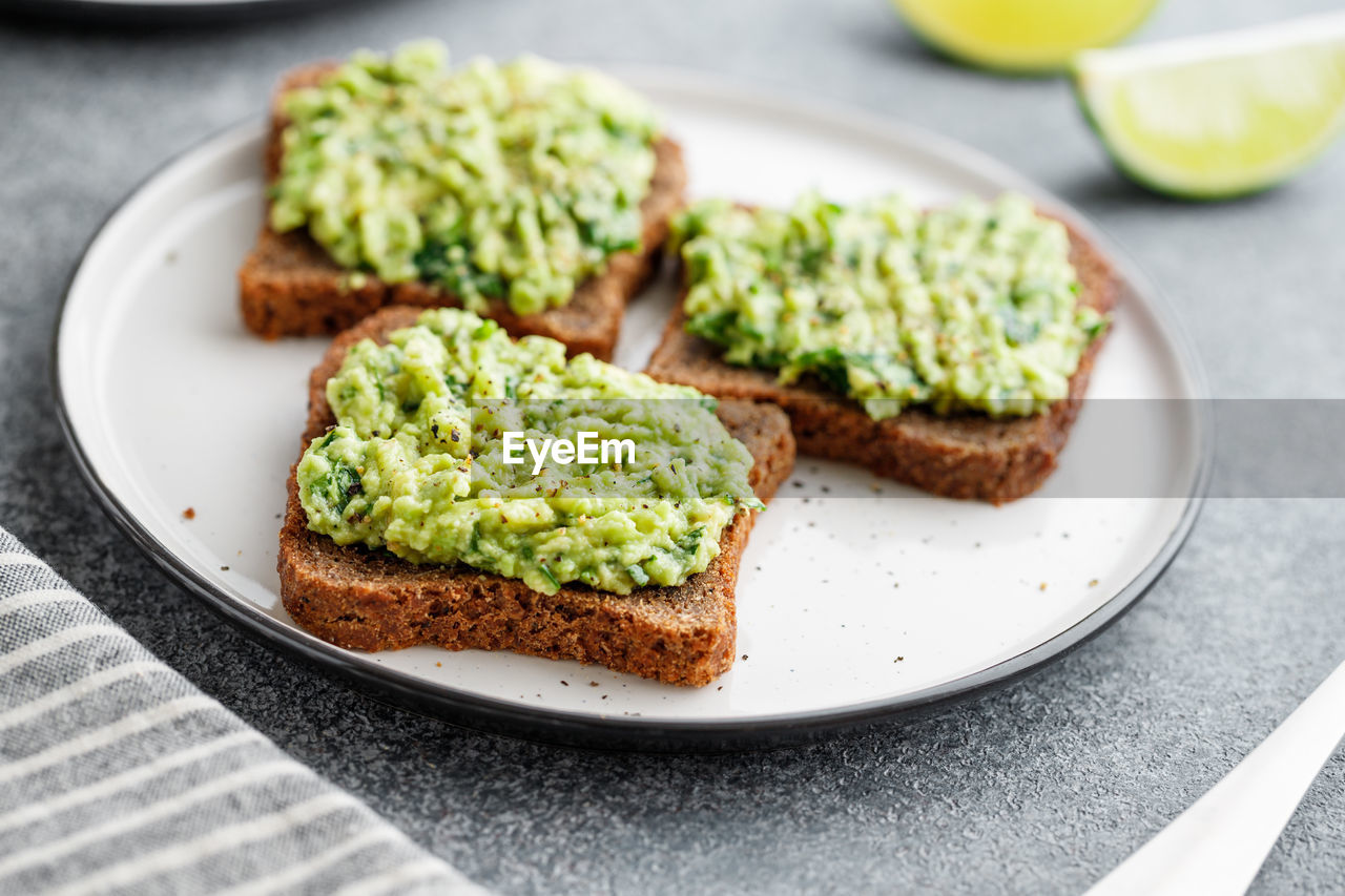 food, food and drink, plate, bread, healthy eating, freshness, indoors, ready-to-eat, wellbeing, close-up, still life, avocado, no people, slice, fruit, table, focus on foreground, green color, vegetable, toasted bread, breakfast, snack, dip, vegetarian food, temptation, brown bread, toast, dieting