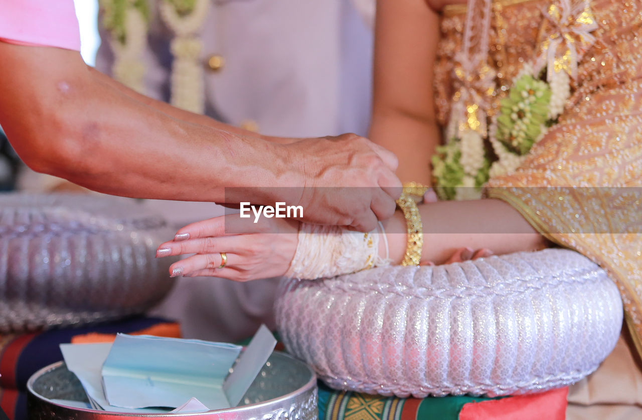 Cropped hand of person performing ritual during wedding ceremony