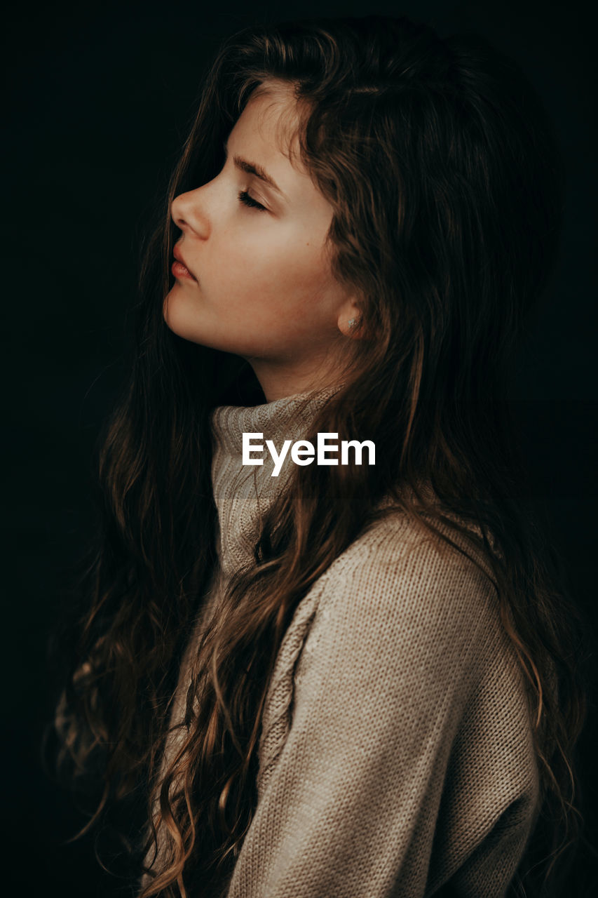 Side View Of Cute Girl With Eyes Closed Against Black Background
