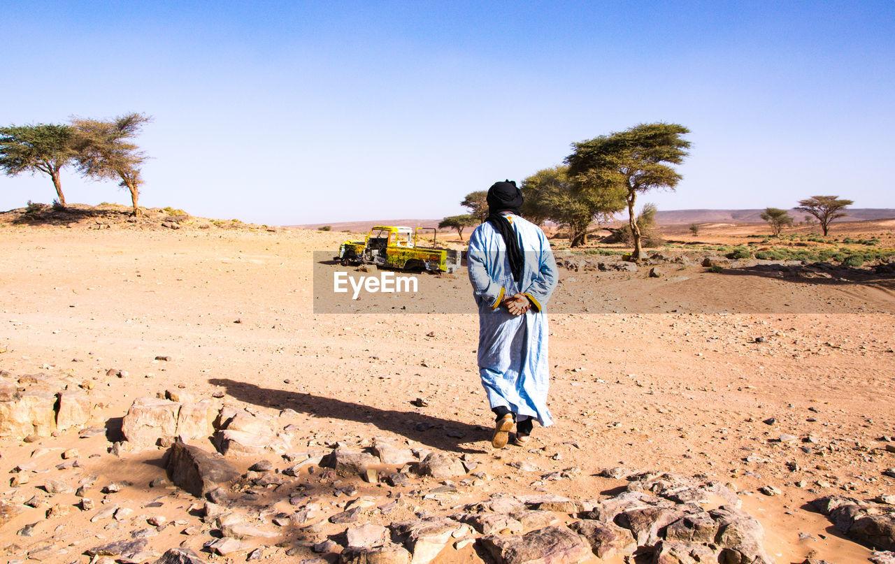 Rear View Of Man Walking At Desert Against Sky