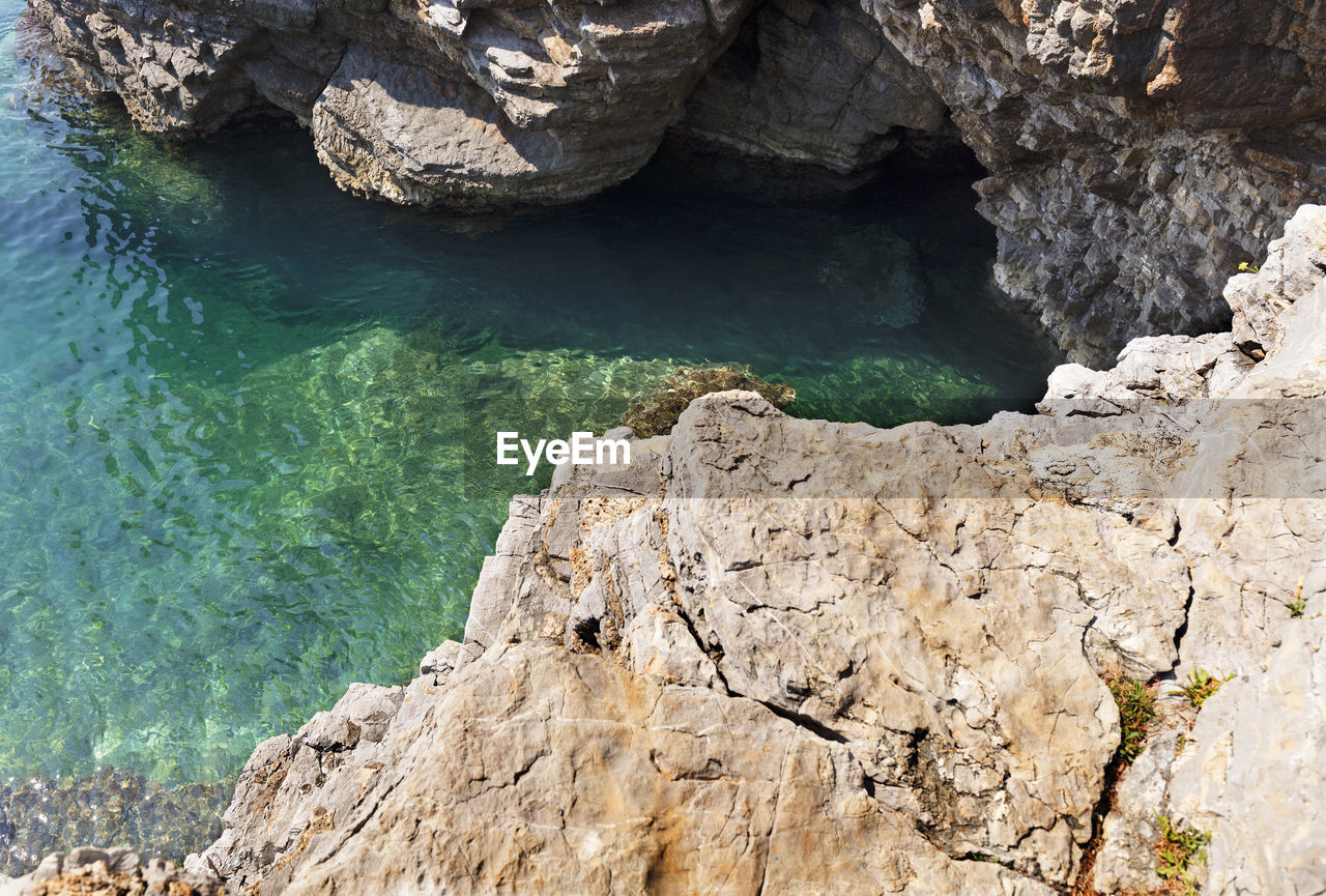 rock, rock - object, solid, water, beauty in nature, rock formation, sea, day, scenics - nature, nature, no people, high angle view, non-urban scene, land, tranquility, cliff, tranquil scene, outdoors, mountain, formation, turquoise colored, eroded
