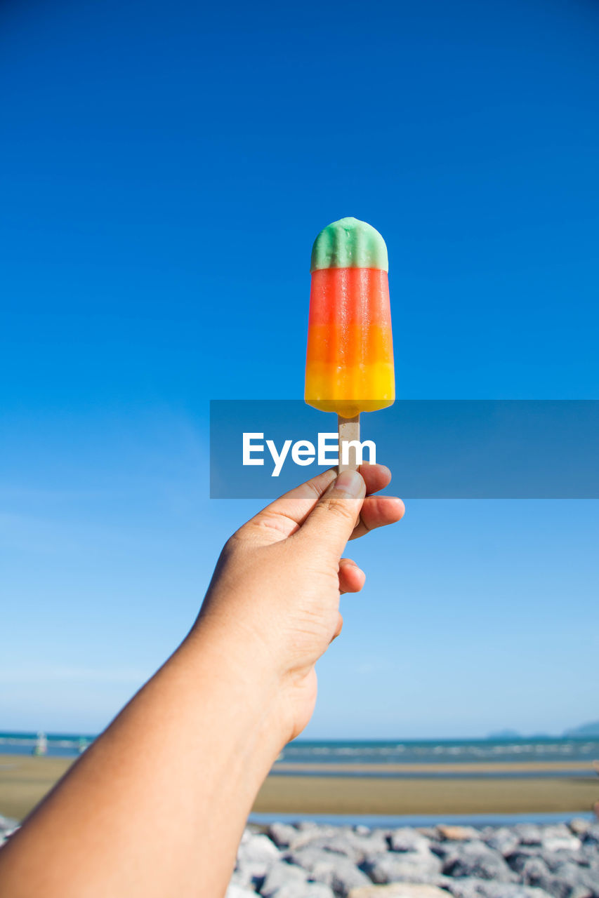 Cropped image of person holding flavored ice cream against sky