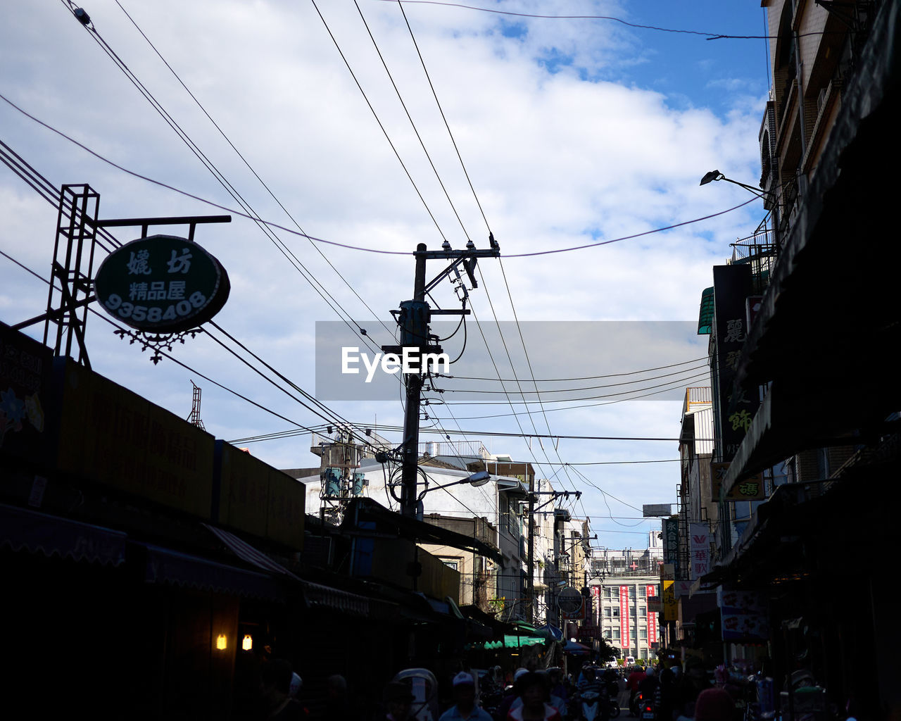 sky, architecture, cable, built structure, building exterior, city, low angle view, cloud - sky, electricity, connection, street, transportation, power line, nature, mode of transportation, technology, group of people, incidental people, outdoors, communication, power supply, light, complexity