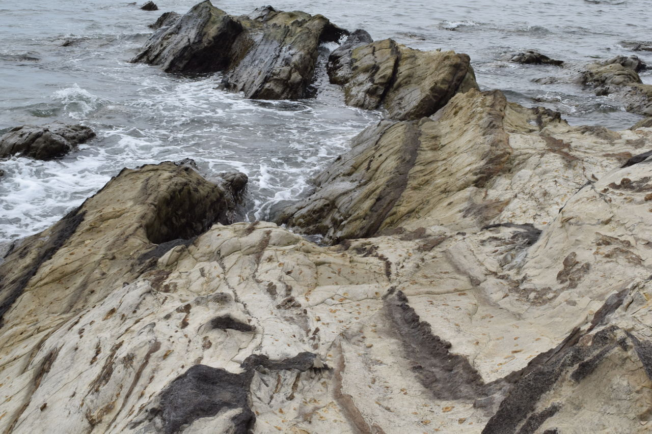 water, rock, sea, motion, rock - object, beauty in nature, land, no people, solid, nature, beach, sport, wave, day, scenics - nature, rock formation, aquatic sport, high angle view, outdoors, power in nature, rocky coastline, flowing water