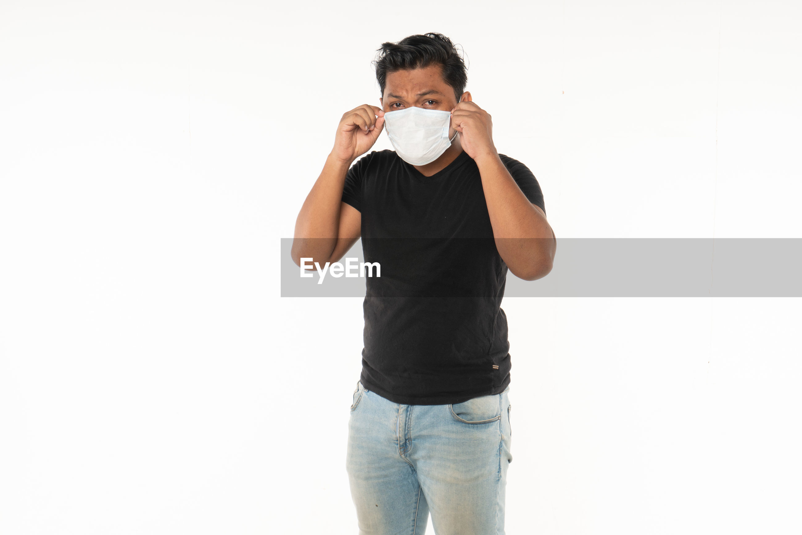 Portrait of man wearing surgical mask while standing against white background