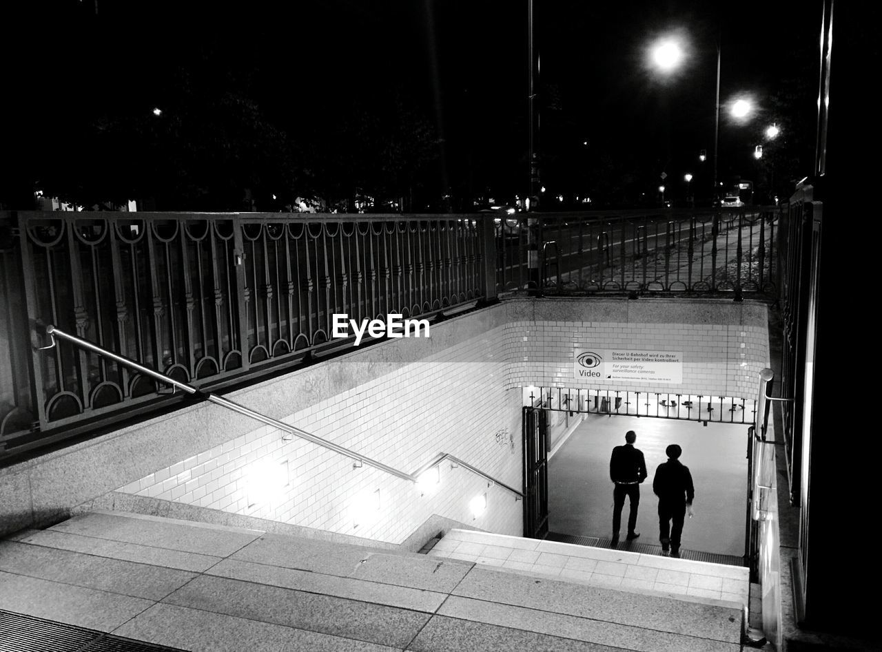 Rear View Of People Walking In Subway At Night