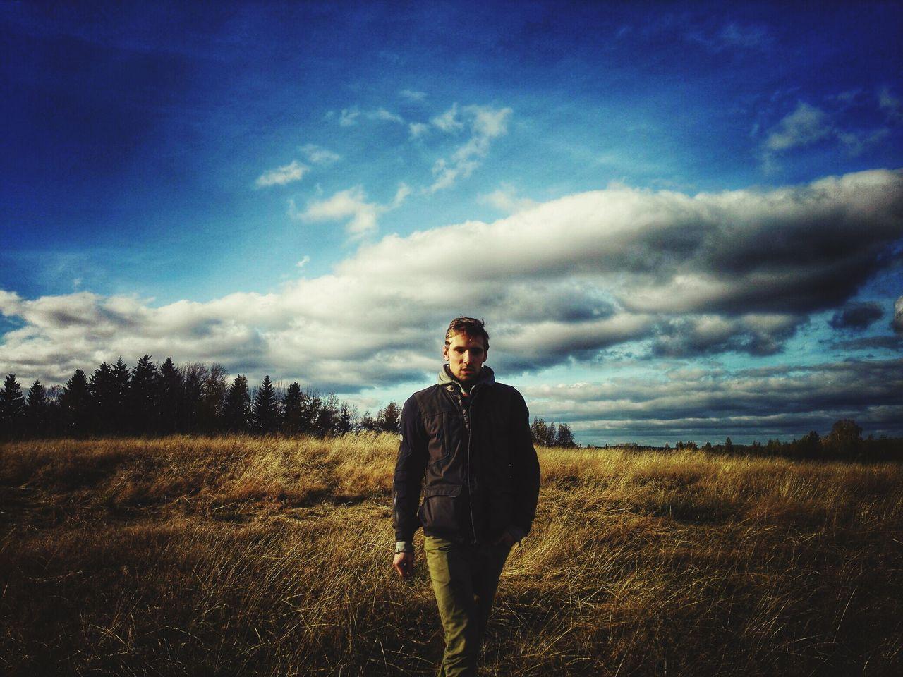 Portrait of man walking on grassy field against blue sky