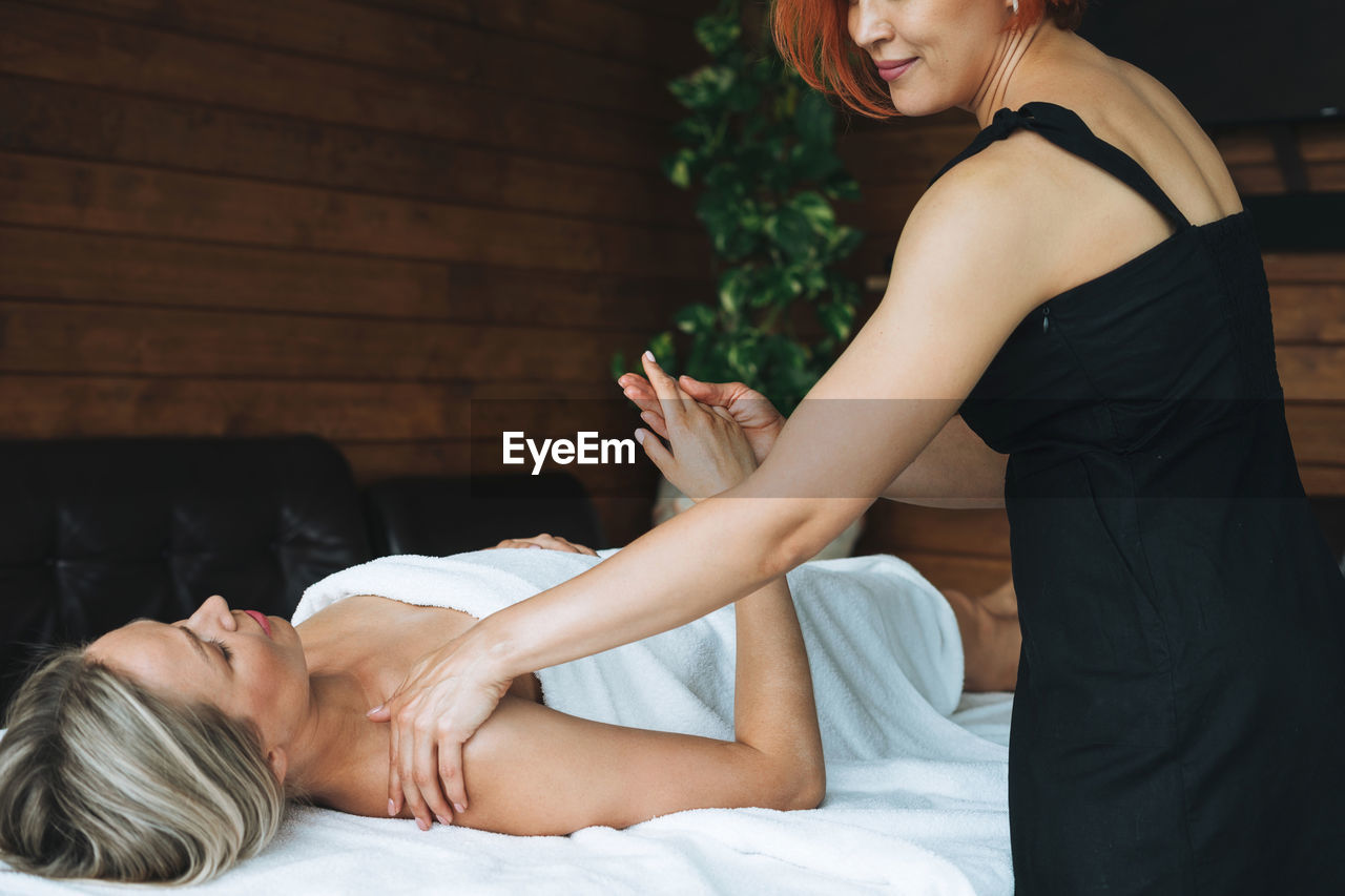 Attractive blonde young woman on couch with white linen enjoys hand body massage in spa