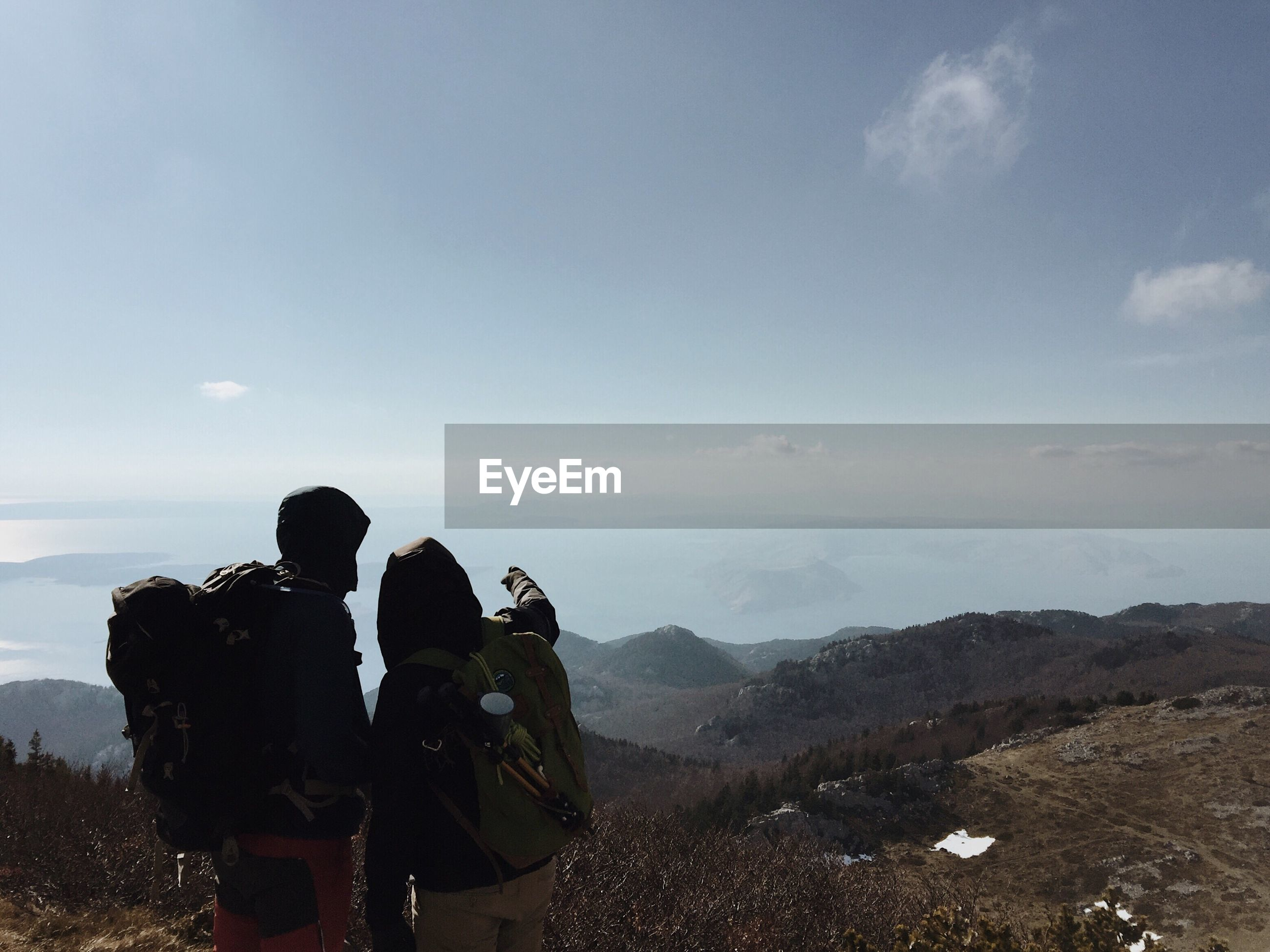 Rear view of hikers standing on mountain against sky