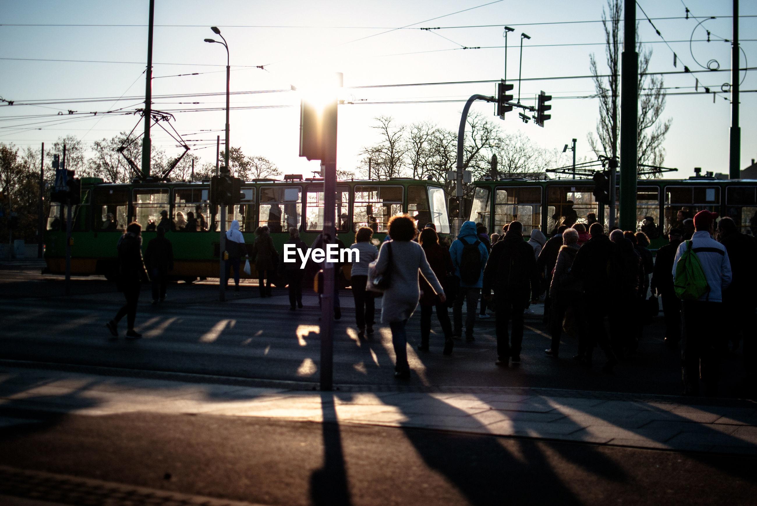 People crossing road by tram against clear sky