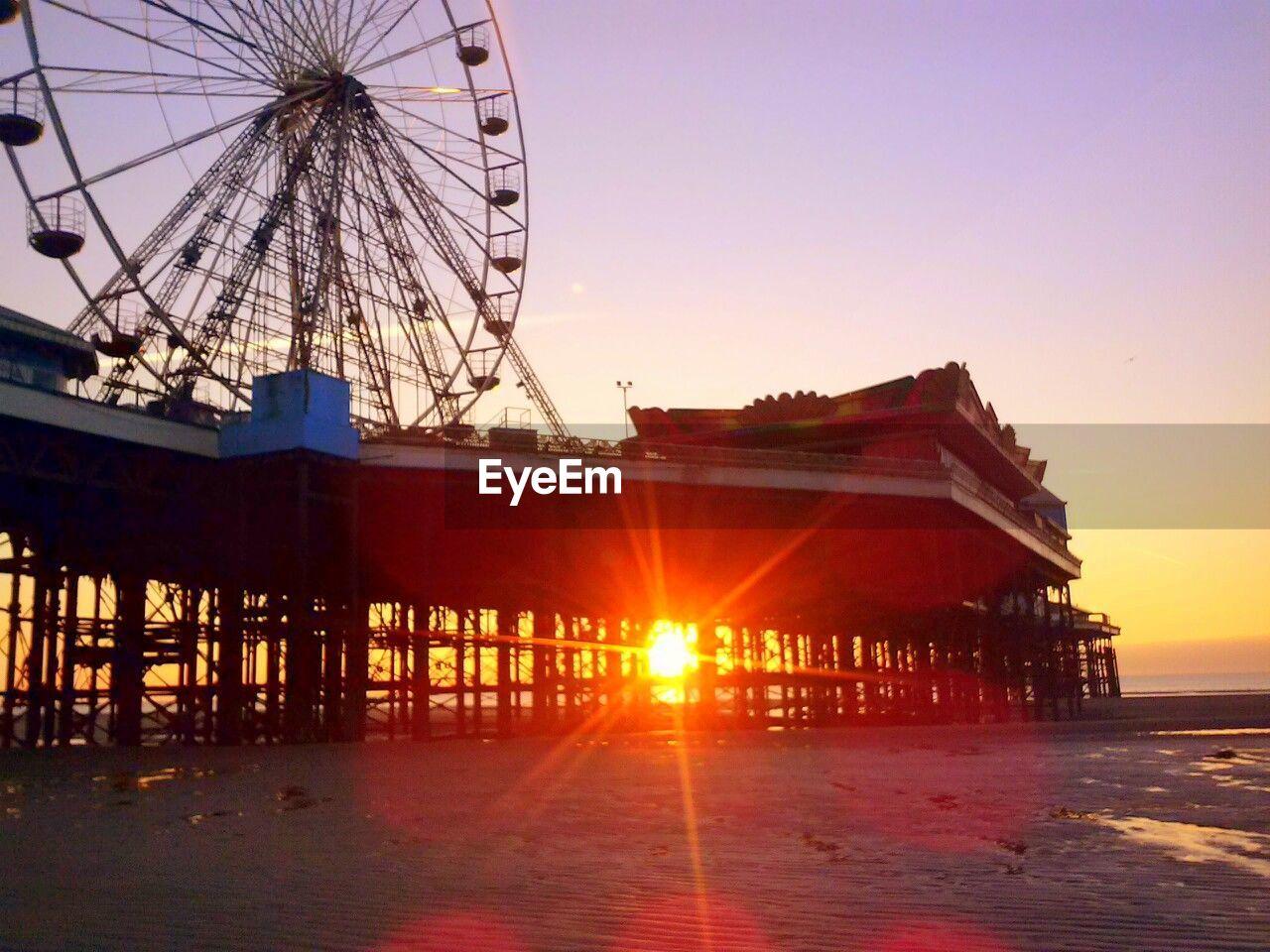 sunset, lens flare, amusement park, sun, outdoors, ferris wheel, clear sky, no people, sunlight, sky, amusement park ride, built structure, arts culture and entertainment, nature, architecture, sea, day