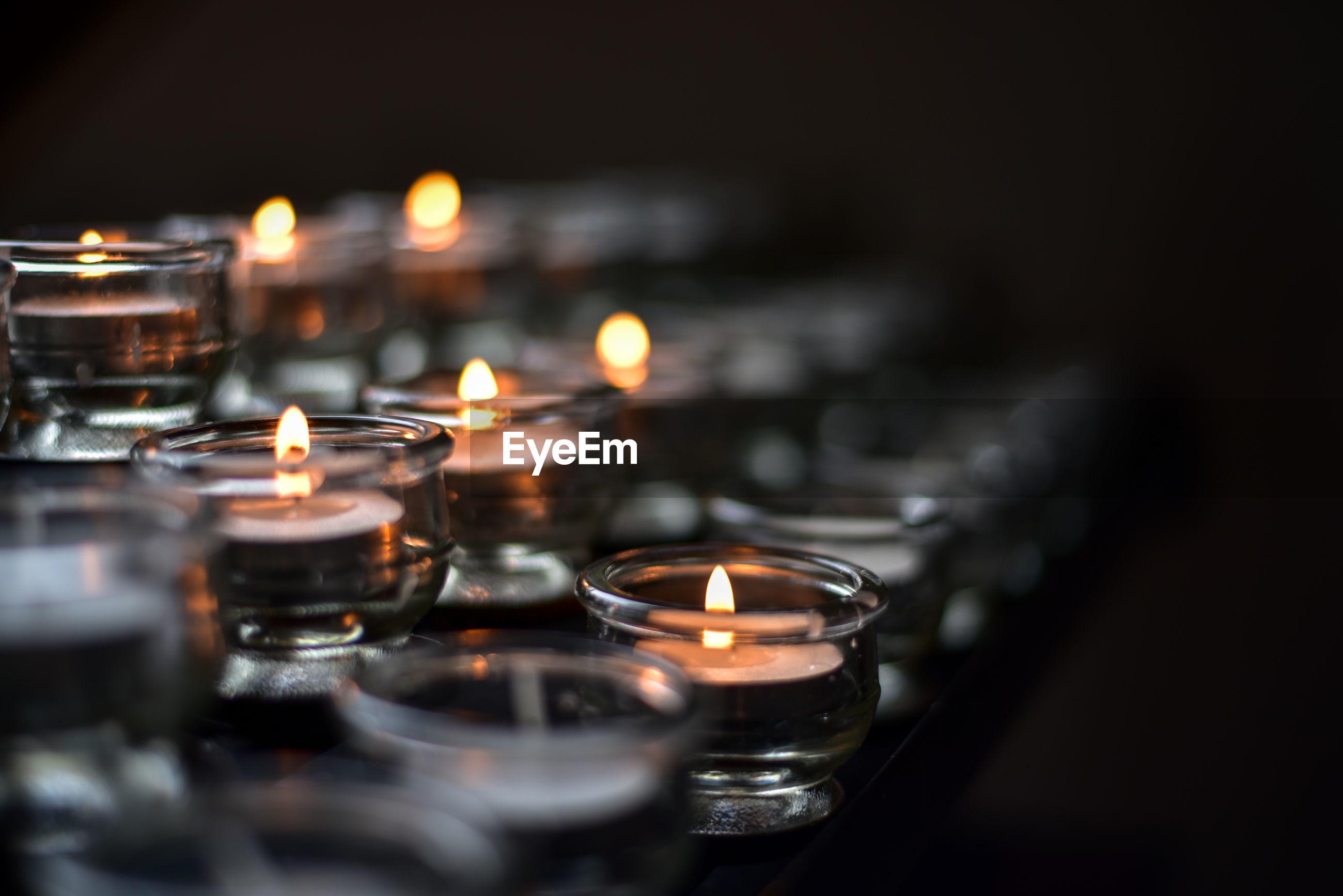Close-up of illuminated tea lights in darkroom