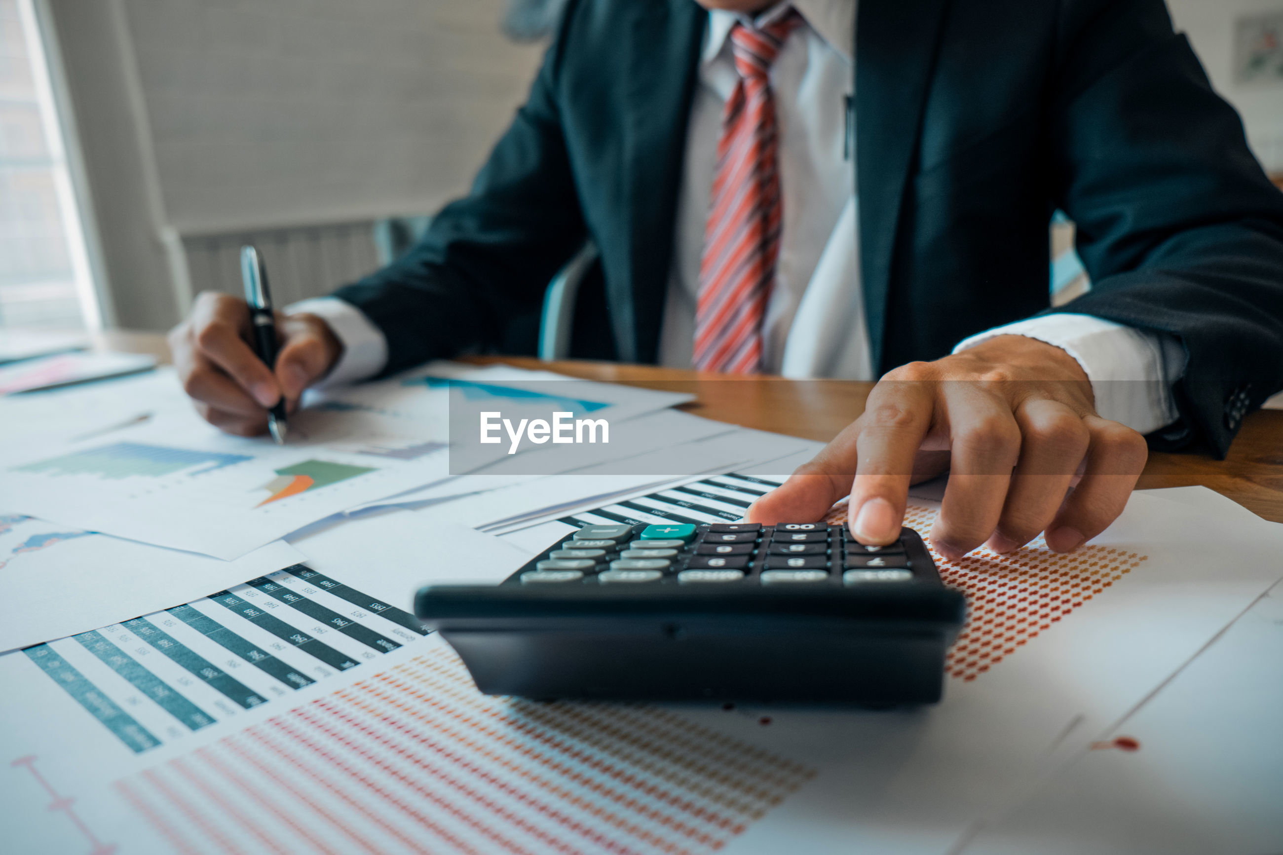 Midsection of businessman working at desk in office