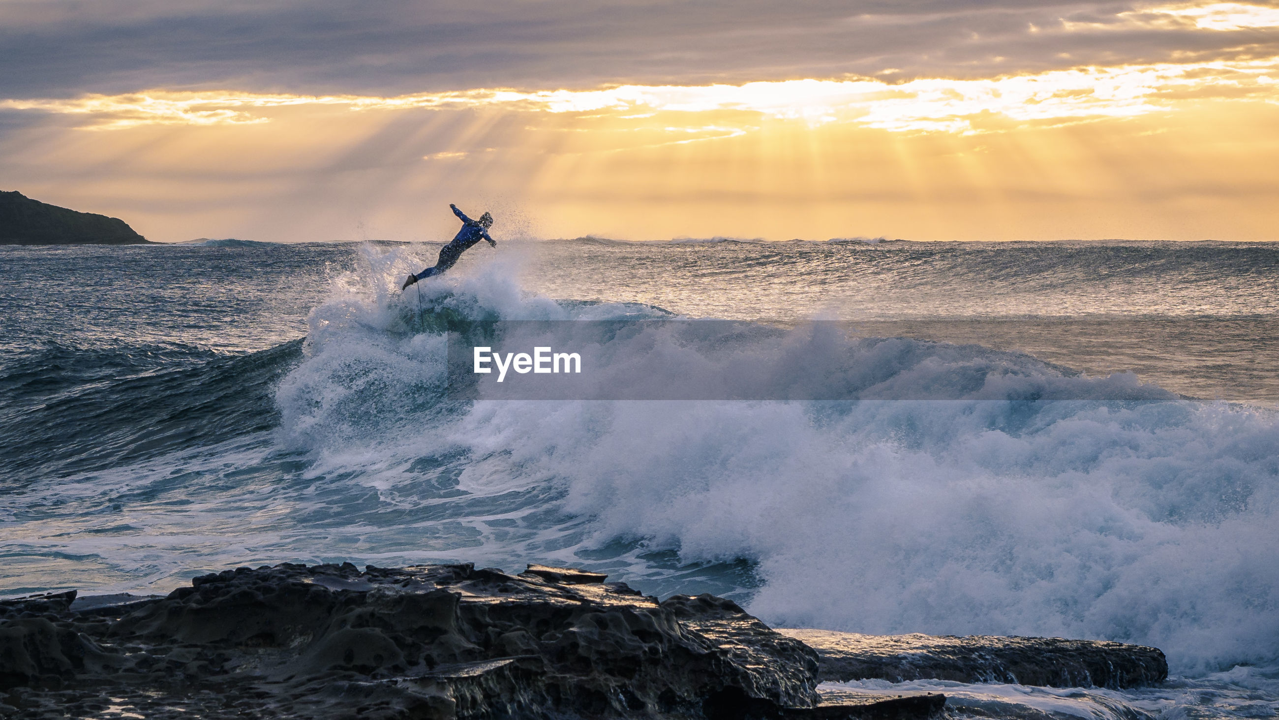 WAVES SPLASHING ON ROCKS AT SUNSET