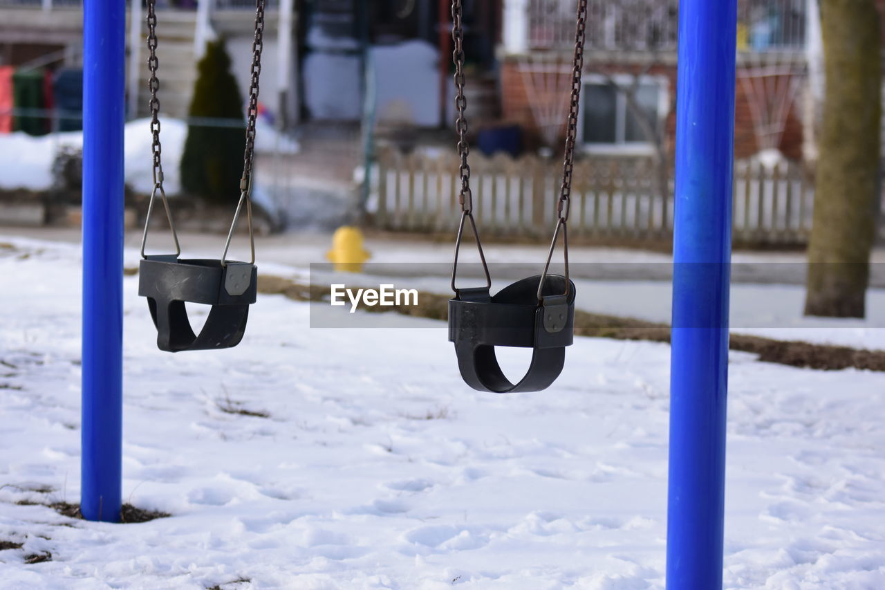 snow, winter, hanging, cold temperature, focus on foreground, playground, day, no people, swing, nature, metal, outdoors, land, field, absence, blue, outdoor play equipment, white color, covering, wheel