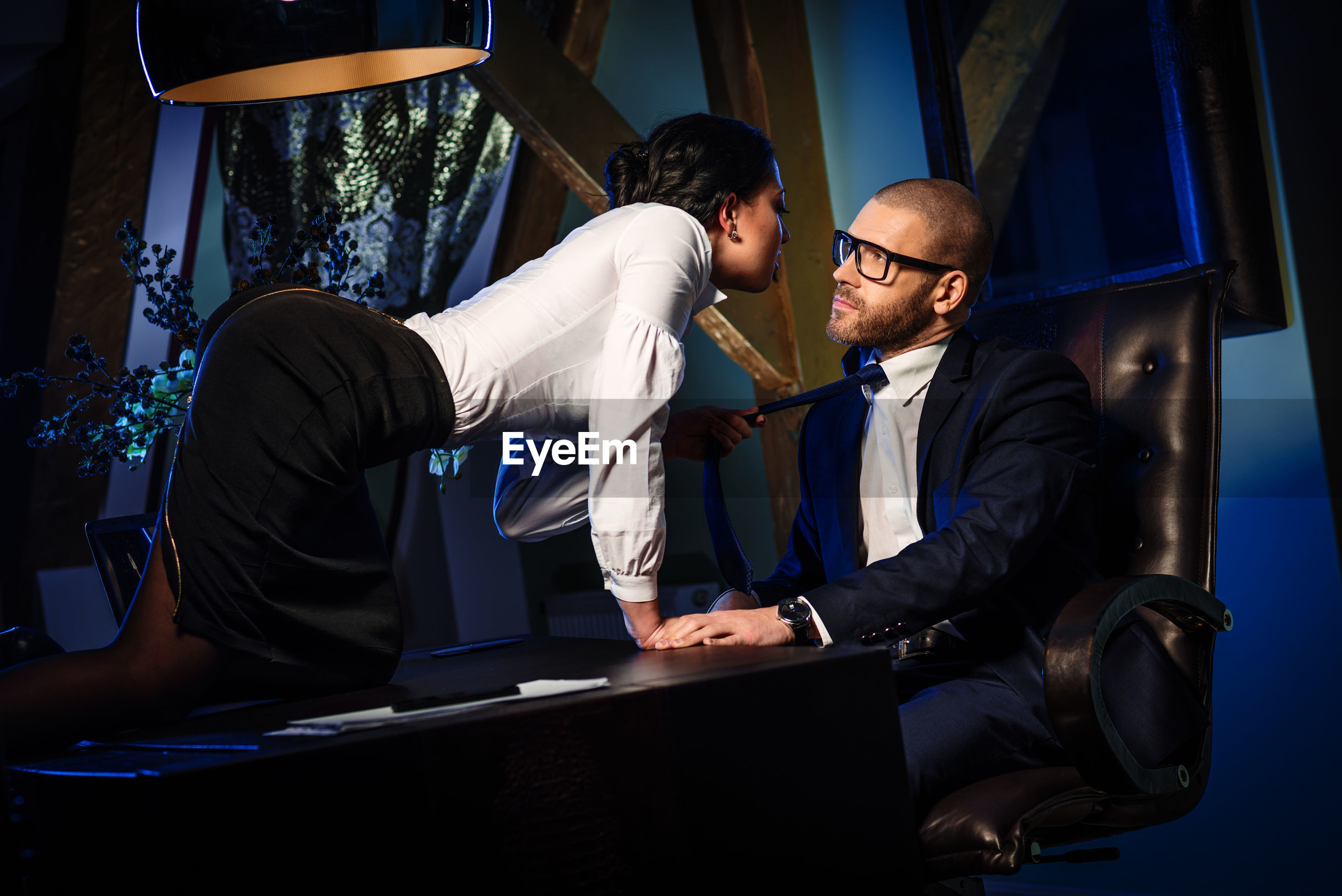 Woman romancing with businessman while kneeling on table in office