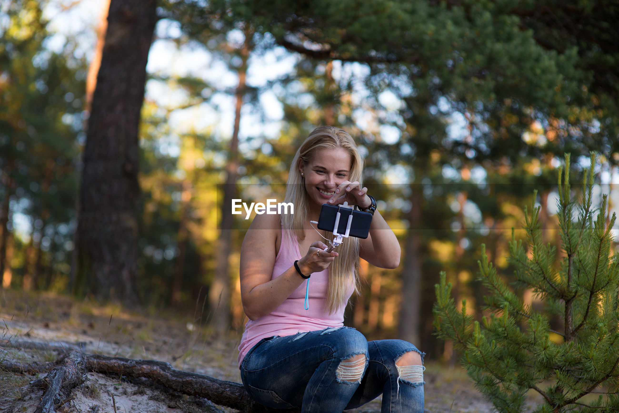 Young woman using mobile phone in forest
