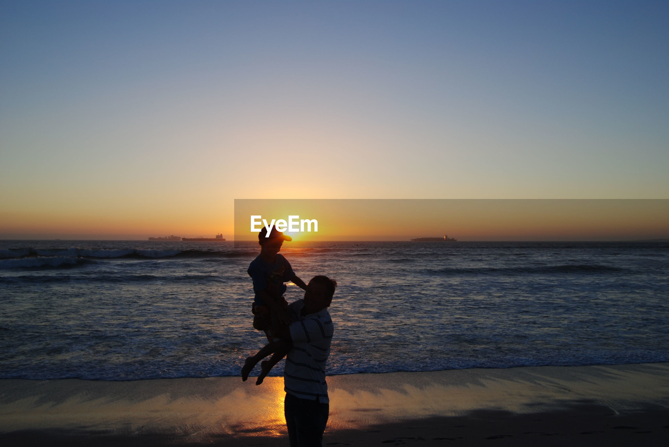 Father carrying son at beach against sky during sunset