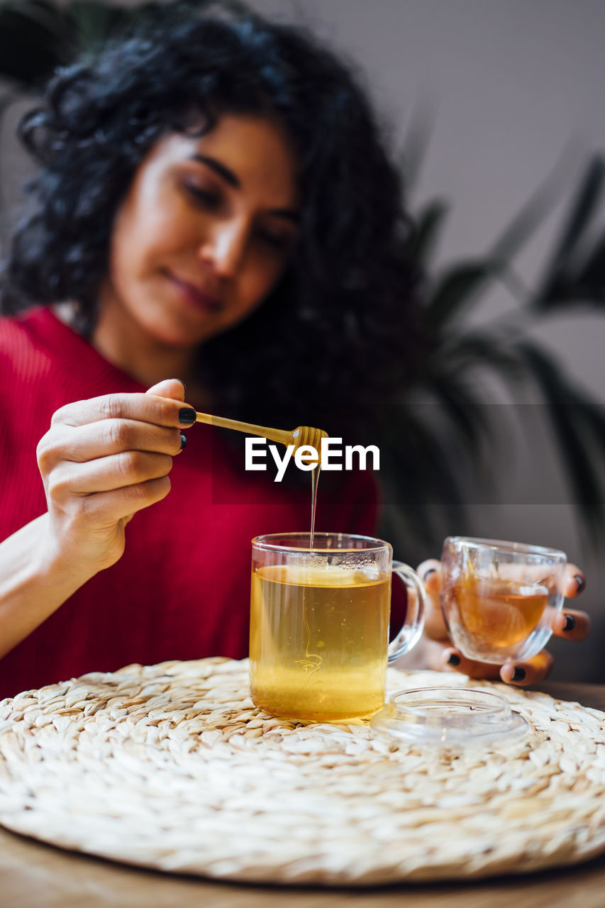 MIDSECTION OF WOMAN WITH DRINK ON TABLE