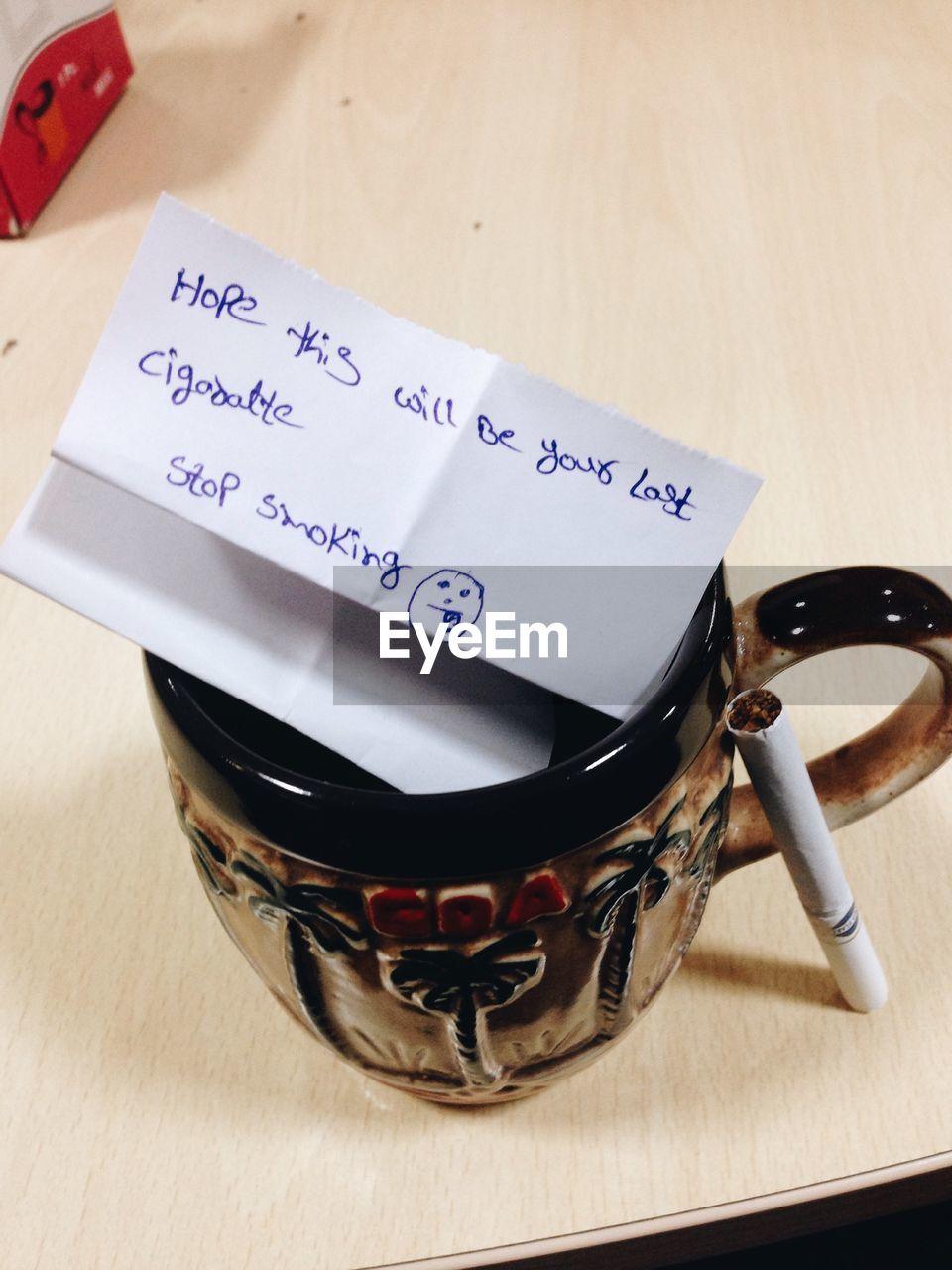High angle view of text on paper over mug