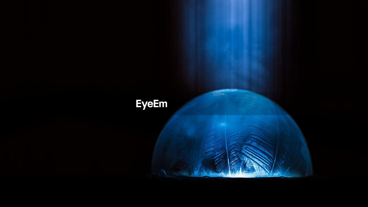 Close-Up Of Frozen Water Drop In Darkroom