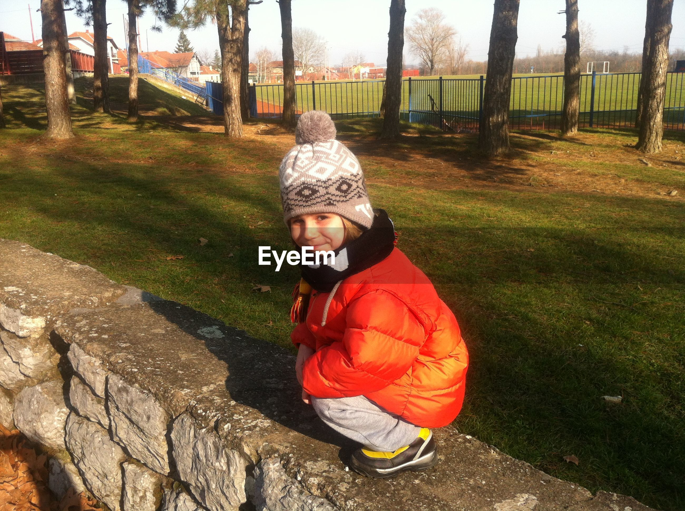 Portrait of boy sitting on wall during winter
