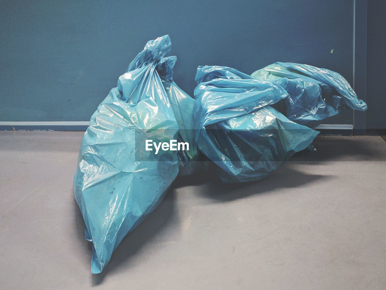 High Angle View Of Blue Garbage Bags On Floor By Wall