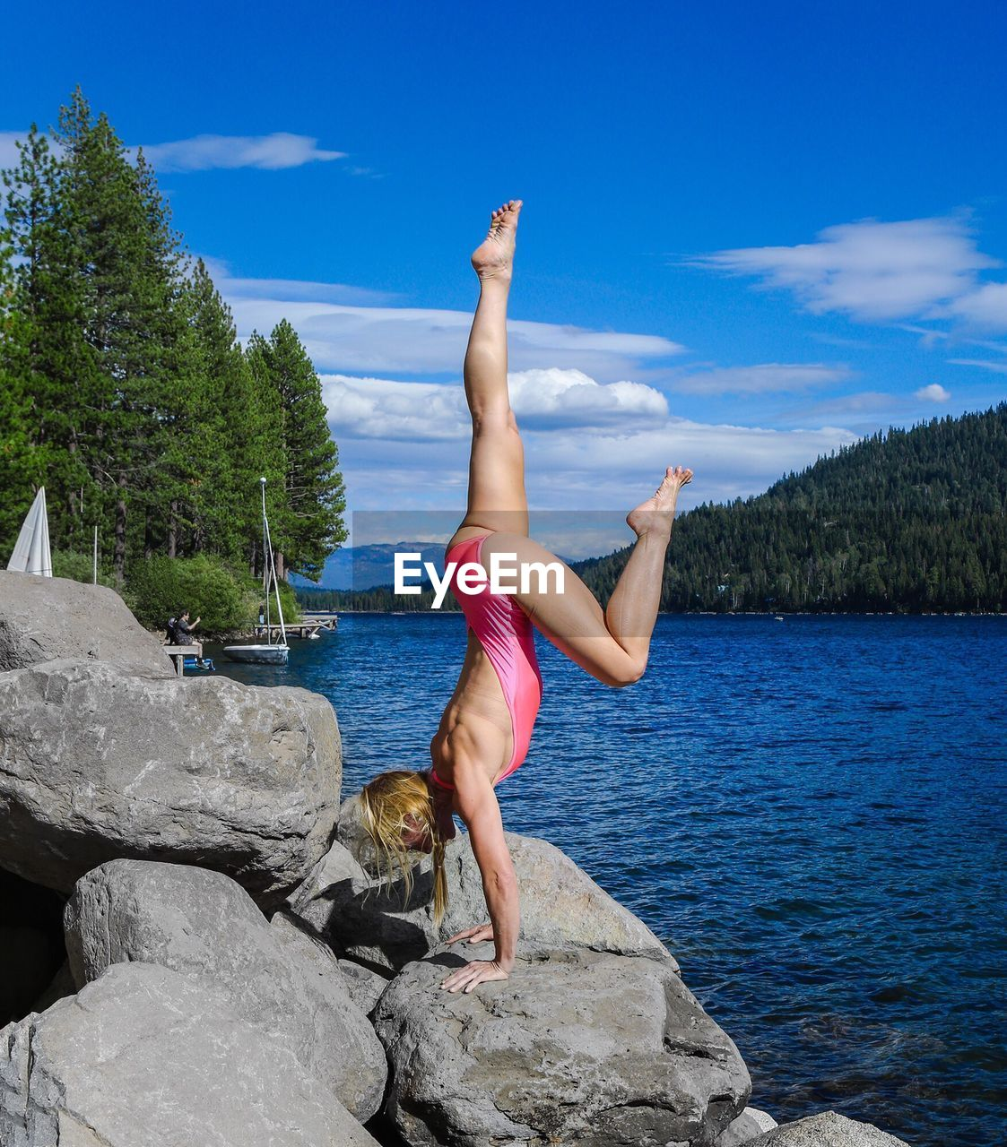 Full length of woman performing a handstand on lake