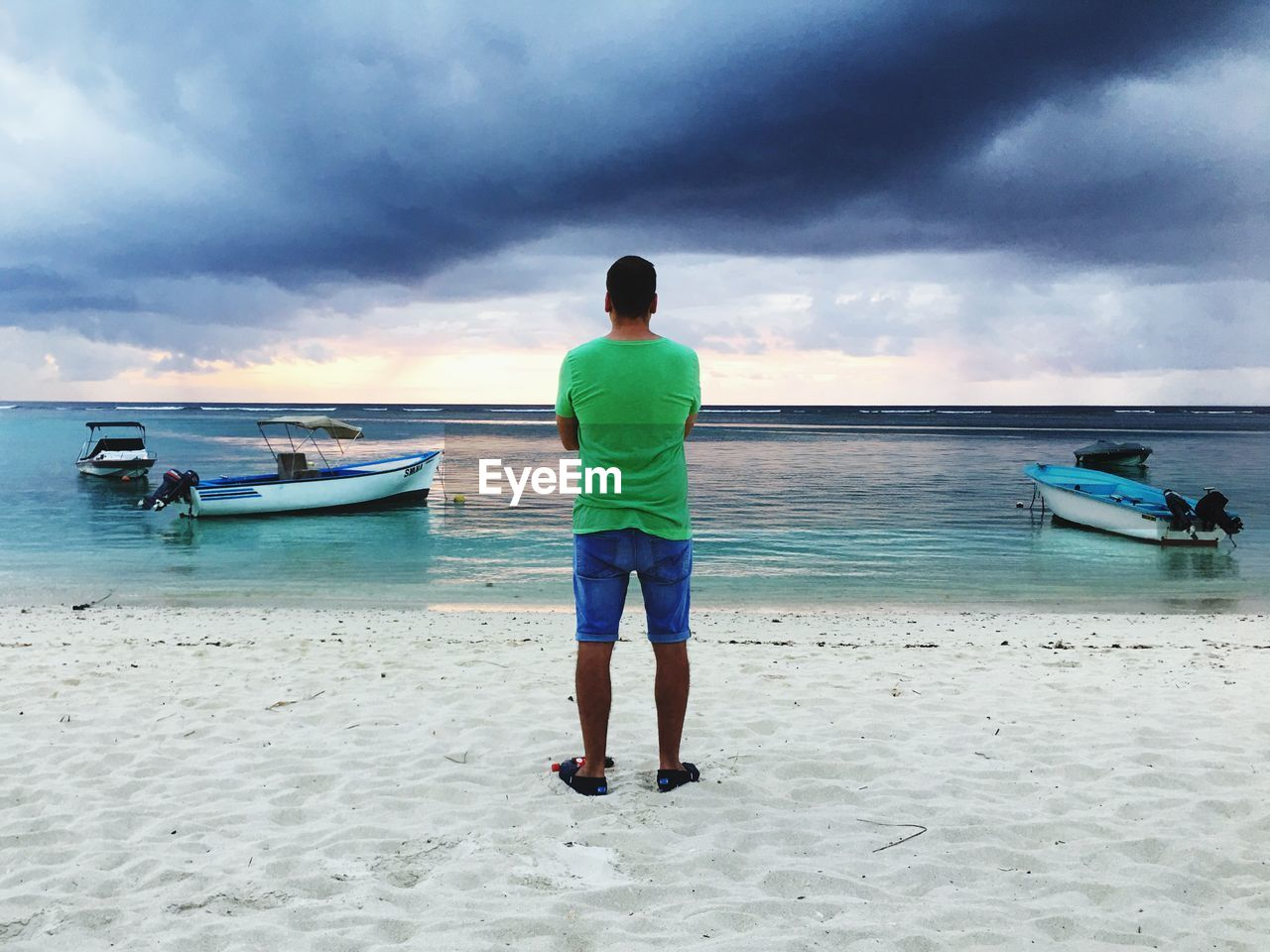 sea, beach, water, sky, cloud - sky, sand, horizon over water, shore, nature, nautical vessel, full length, one person, transportation, scenics, standing, mode of transport, rear view, real people, beauty in nature, moored, casual clothing, outdoors, men, day, one man only, young adult, adult, people