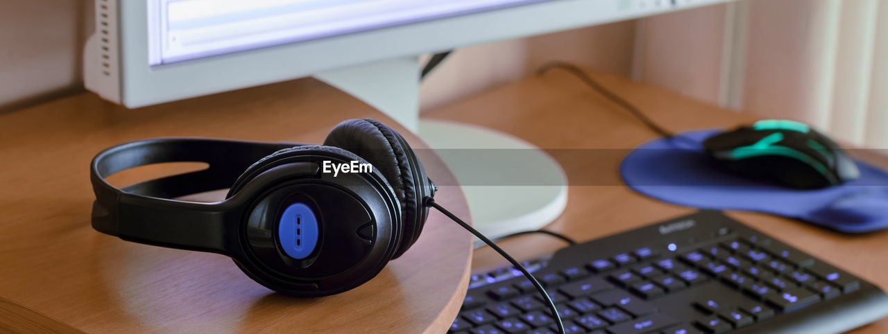 technology, table, computer, indoors, connection, still life, computer equipment, focus on foreground, wireless technology, close-up, no people, communication, music, keyboard, computer keyboard, computer mouse, furniture, headphones, equipment, high angle view