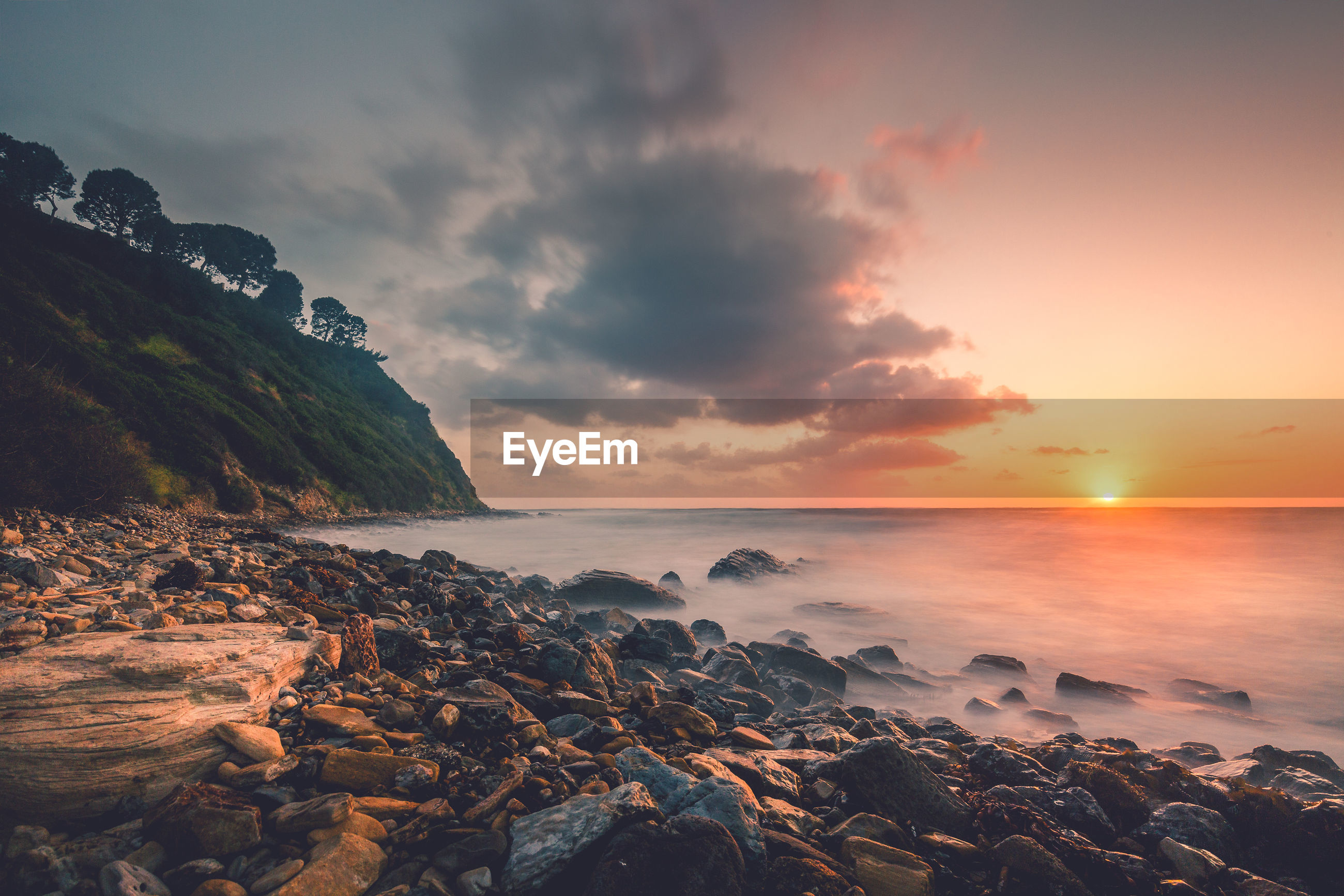 Scenic view of sunset at rocky shore by sea against sky