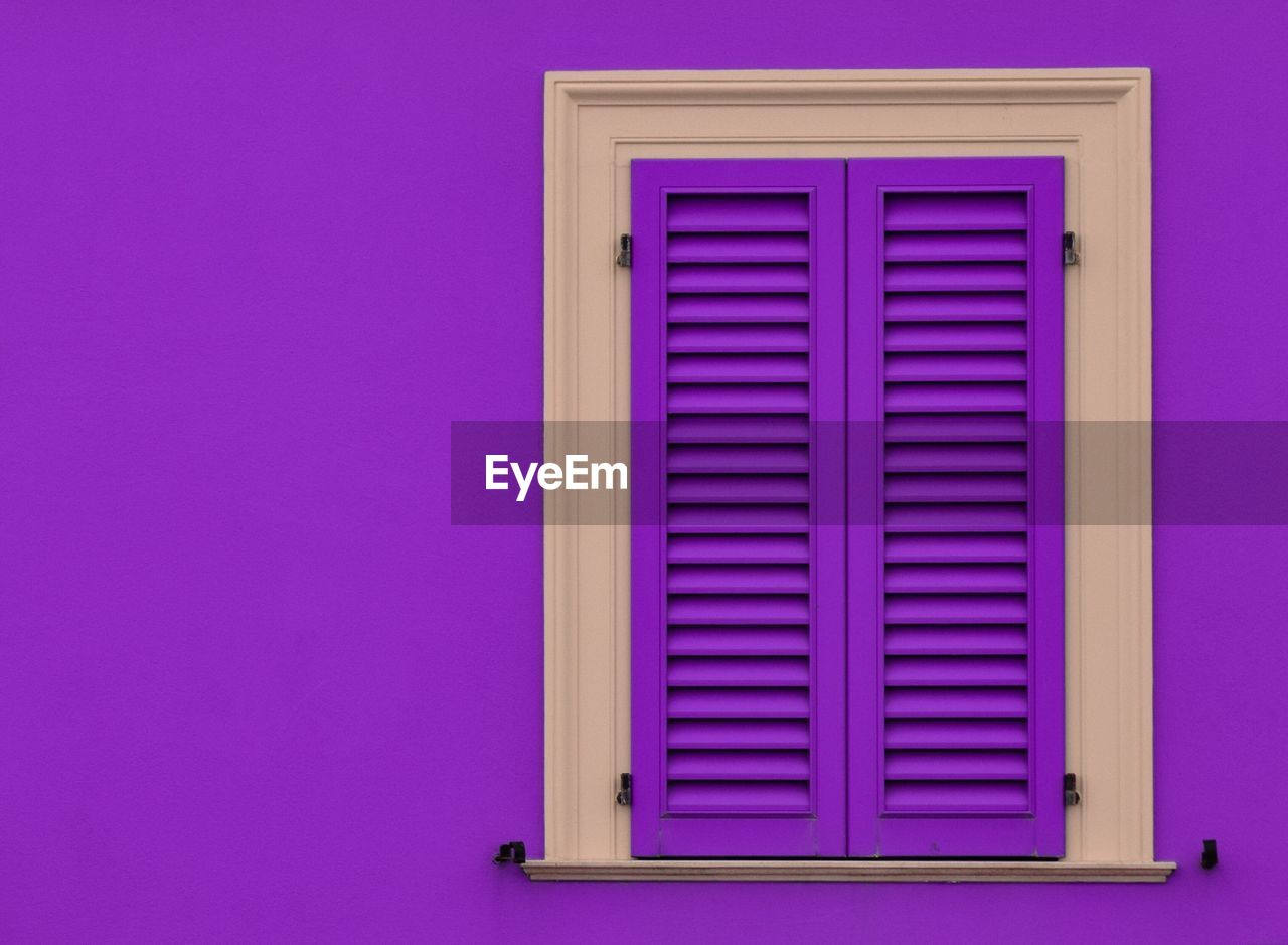 Closed wooden window on lavender wall of house