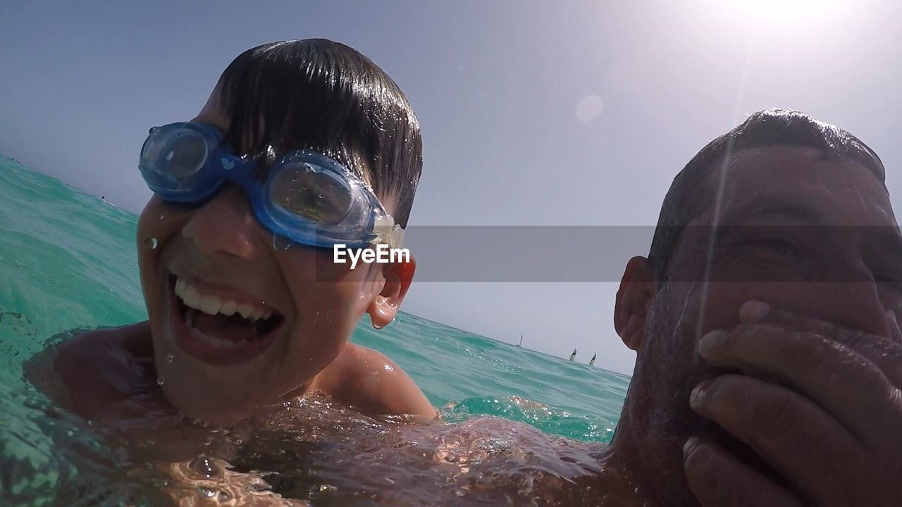 Close-up of cheerful son and father swimming in sea against sky
