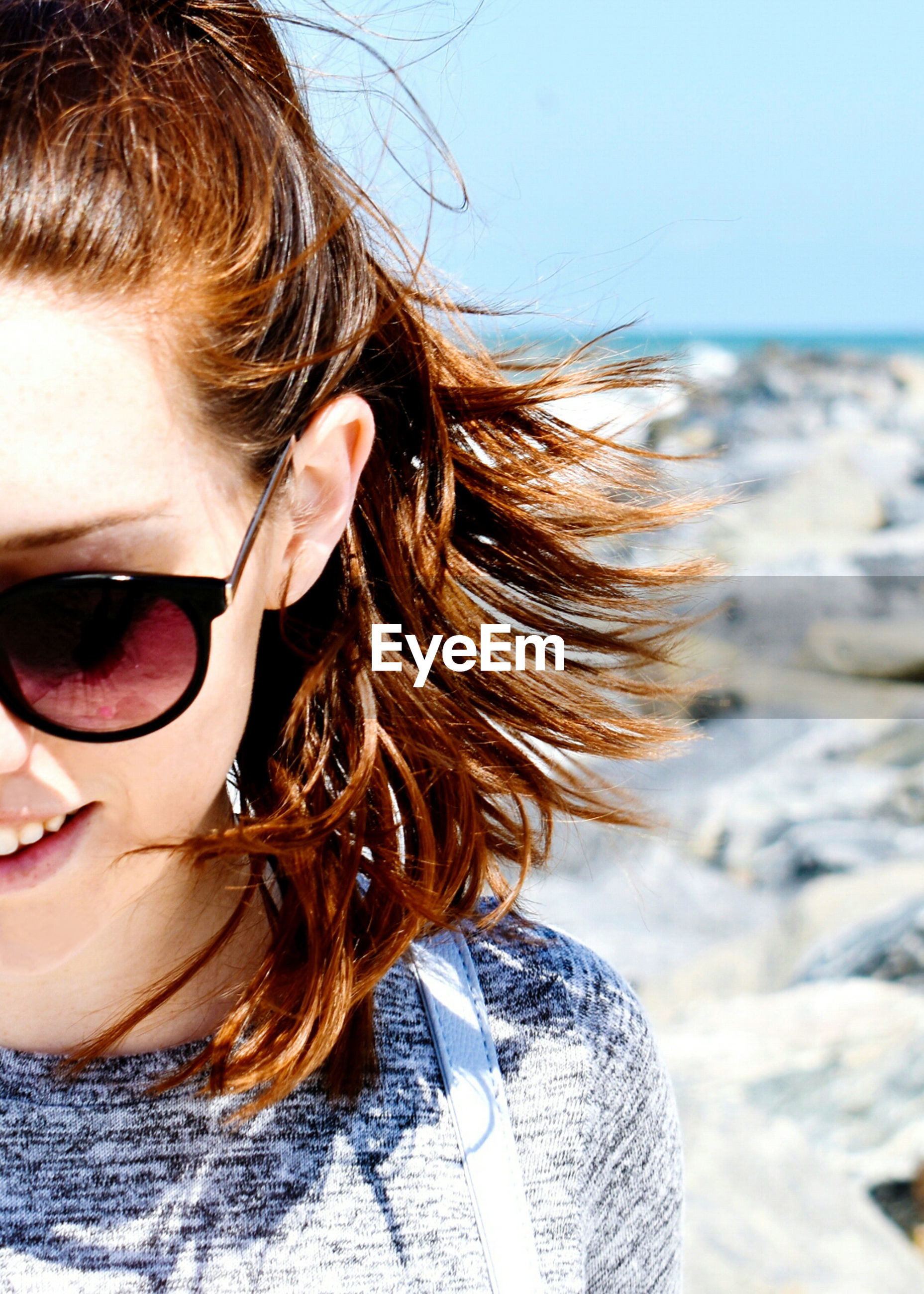 Close-up of woman wearing sunglasses against rocks and sky
