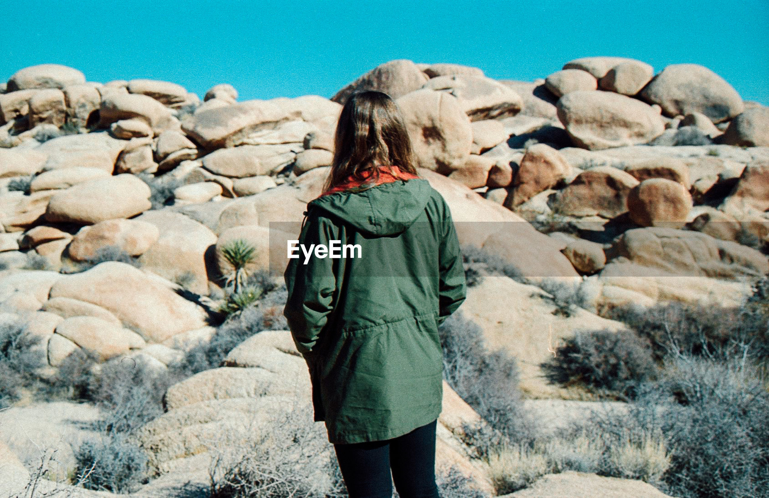 Rear view of woman standing by rocks against clear sky