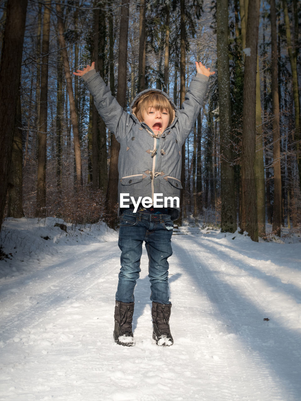 Full Length Of Boy With Arms Raised Standing On Snow Covered Forest