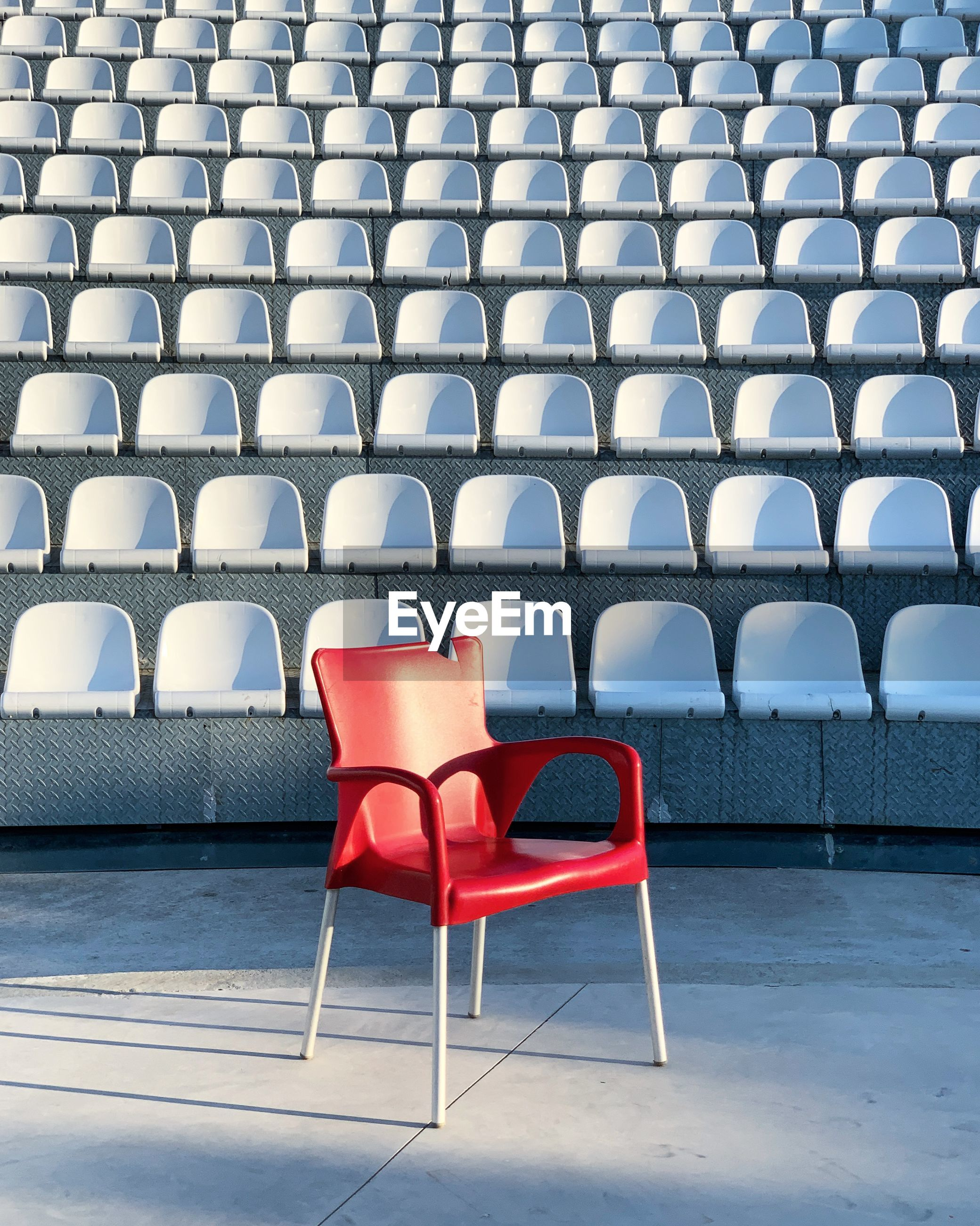 Empty red chair against white bleachers at stadium