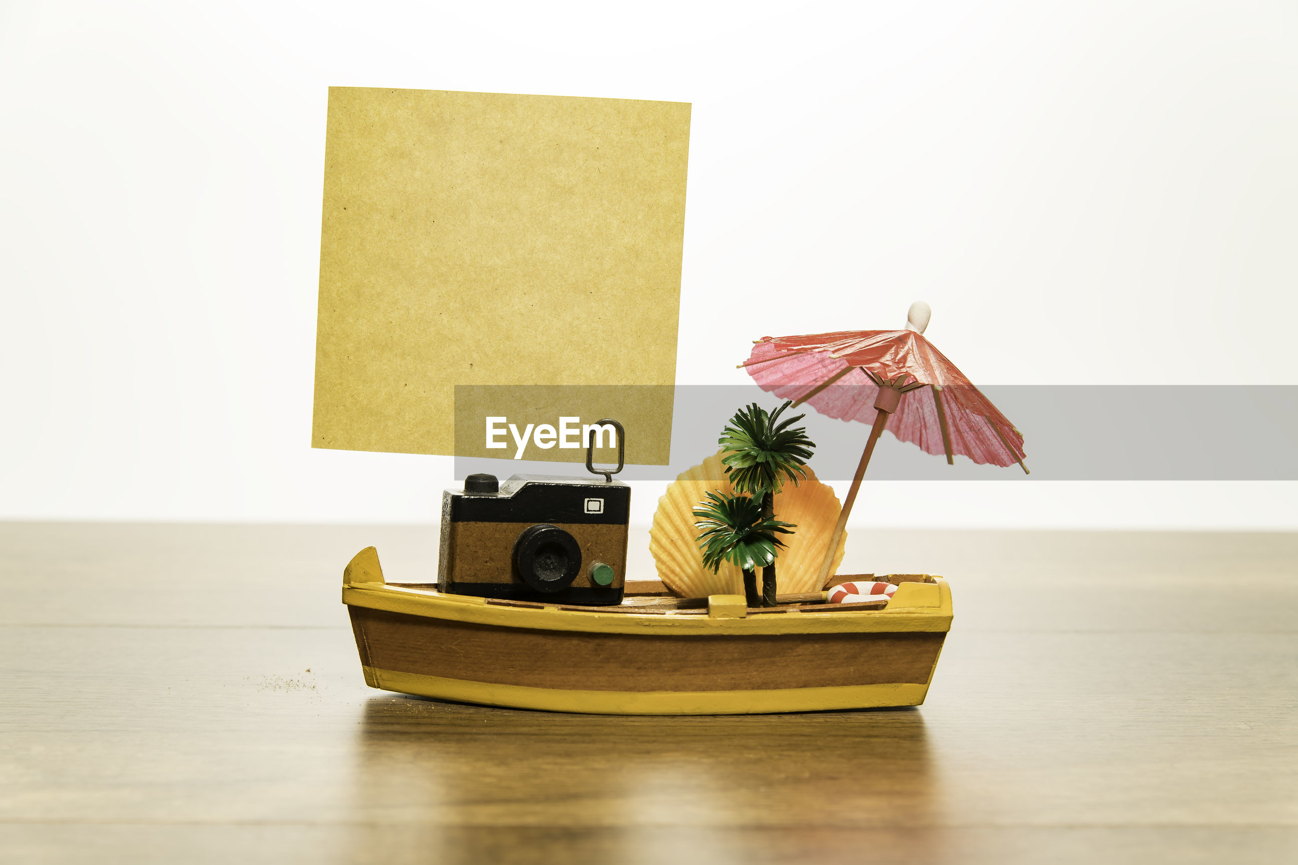 Container on boat on table against white background