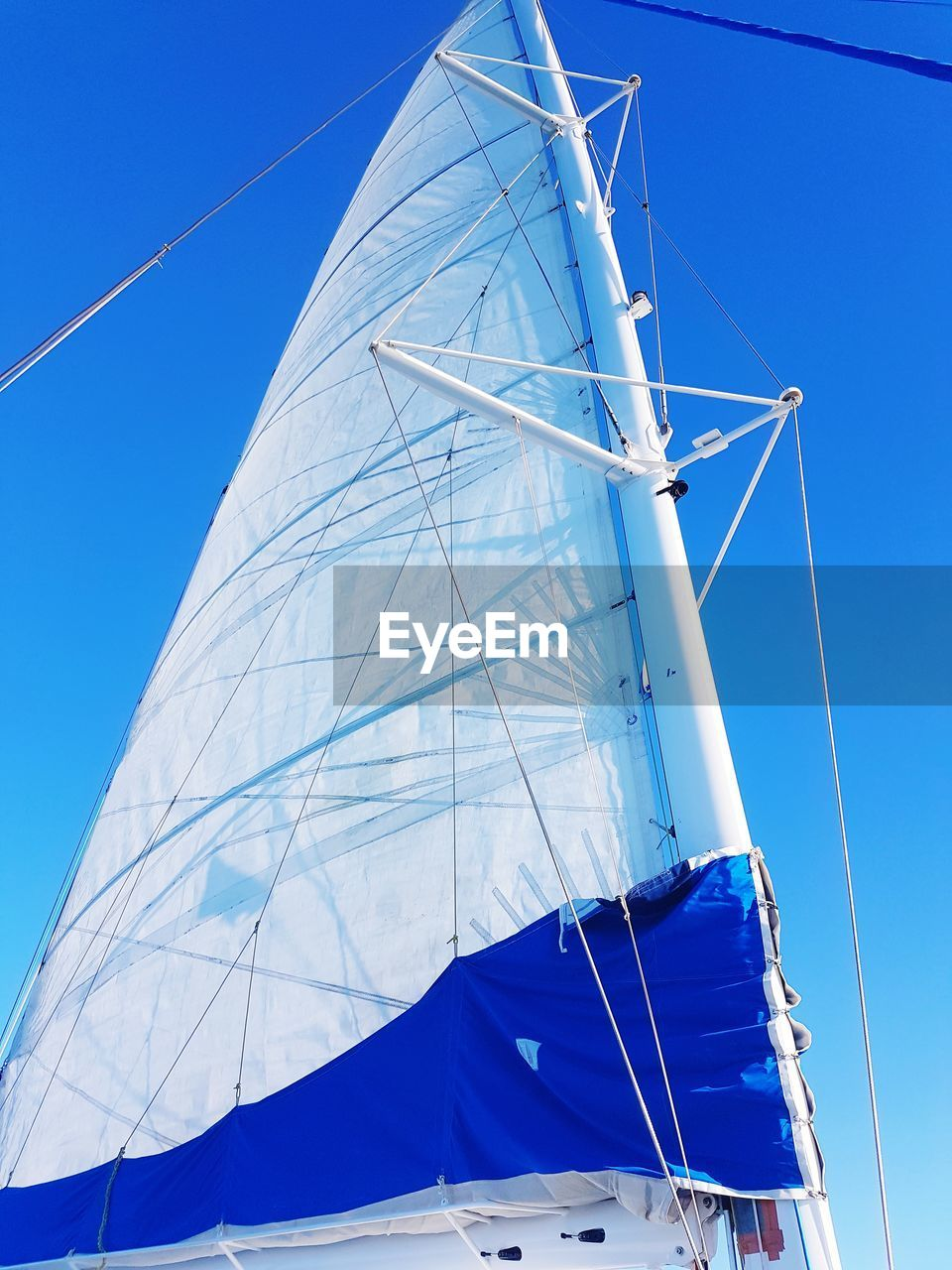 blue, sky, low angle view, nature, sailboat, day, clear sky, nautical vessel, canvas, no people, environment, mast, pole, white color, textile, sunlight, wind, outdoors, transportation, mode of transportation