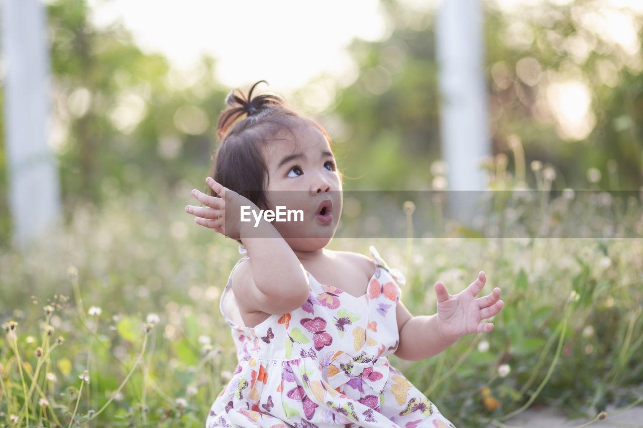 FULL LENGTH OF CUTE BABY GIRL IN SUNLIGHT