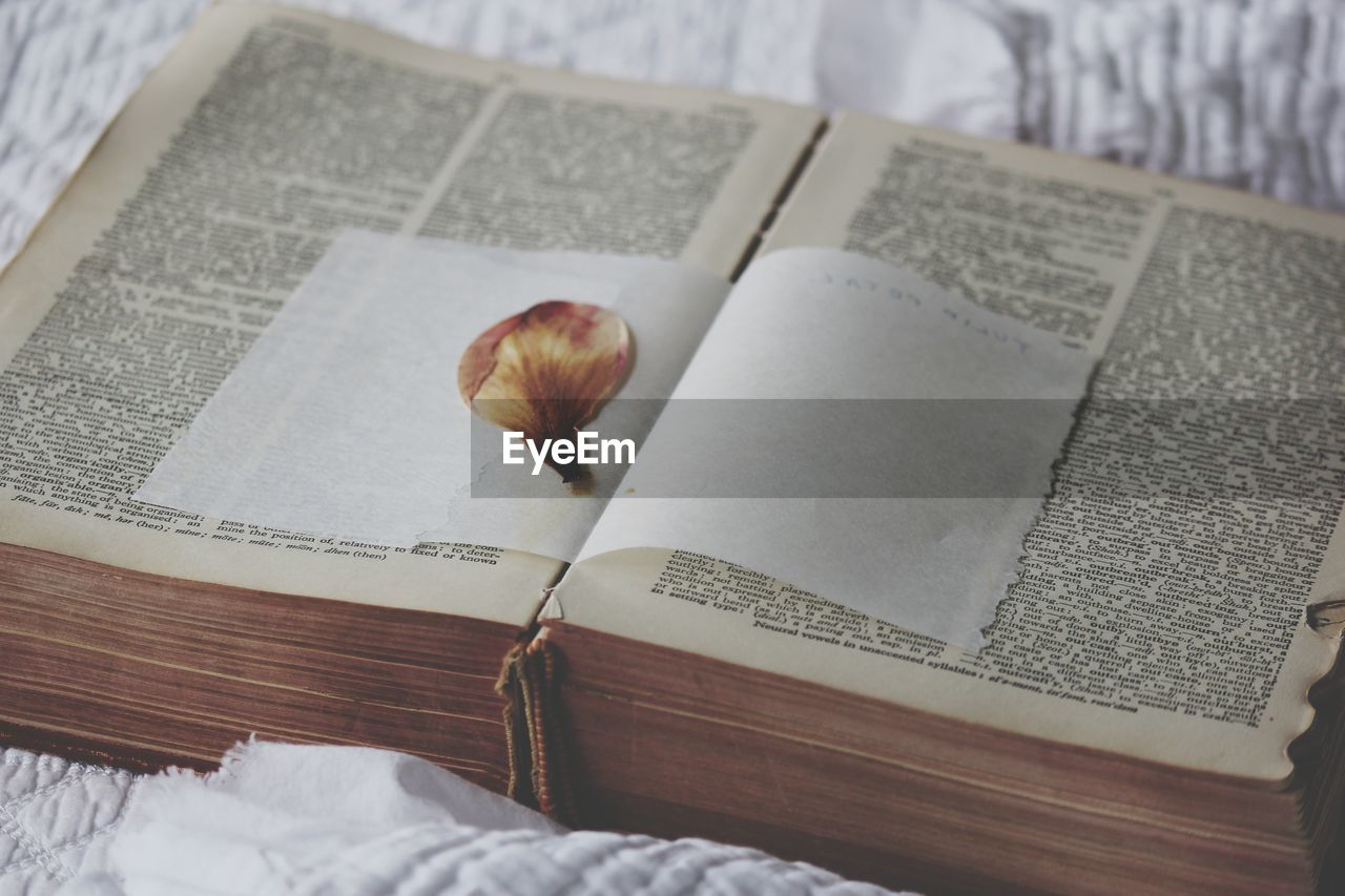 HIGH ANGLE VIEW OF OPEN BOOK ON PAPER