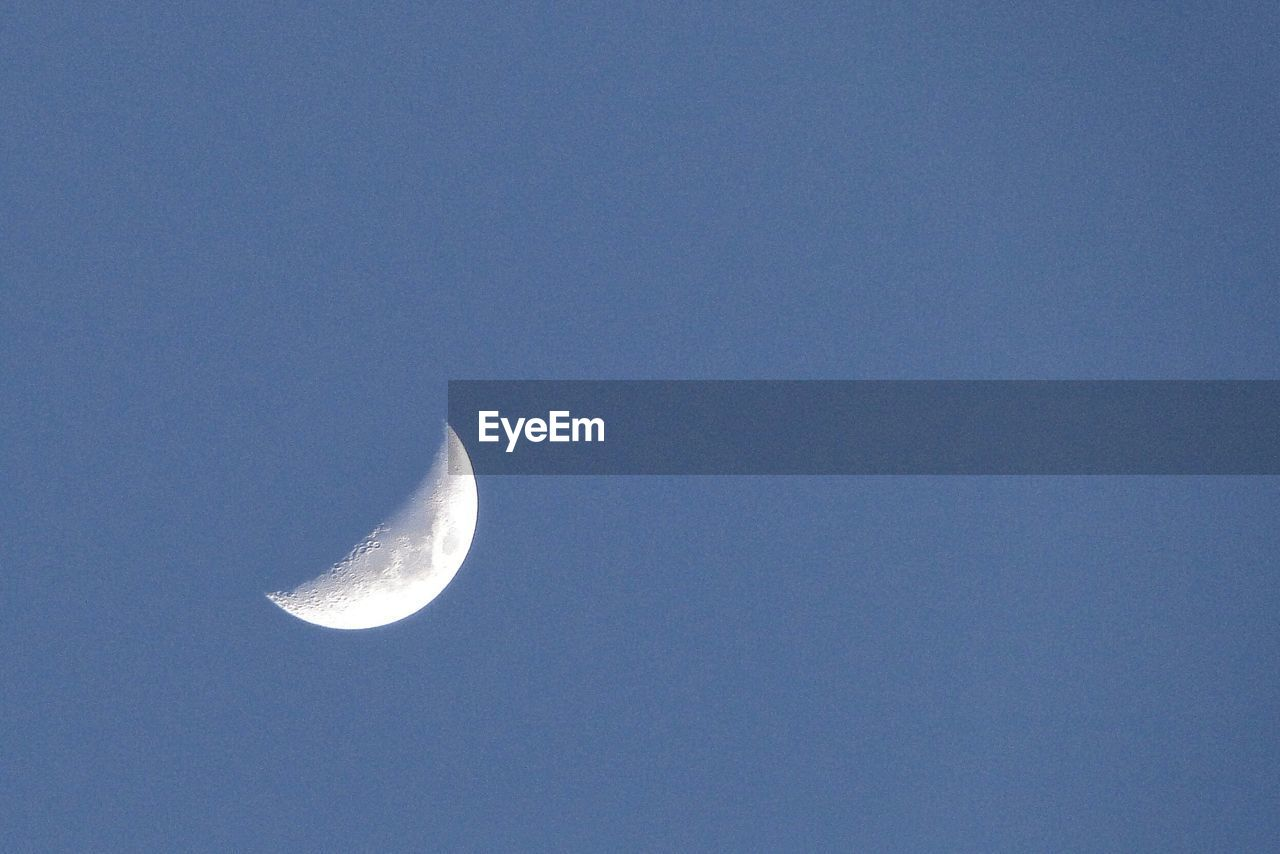 LOW ANGLE VIEW OF HALF MOON AGAINST CLEAR SKY