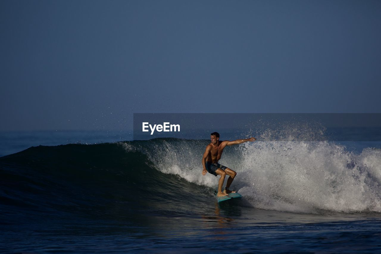 sport, sea, water, one person, motion, aquatic sport, adventure, surfing, extreme sports, leisure activity, full length, nature, men, sky, splashing, copy space, wave, day, skill, outdoors, freedom