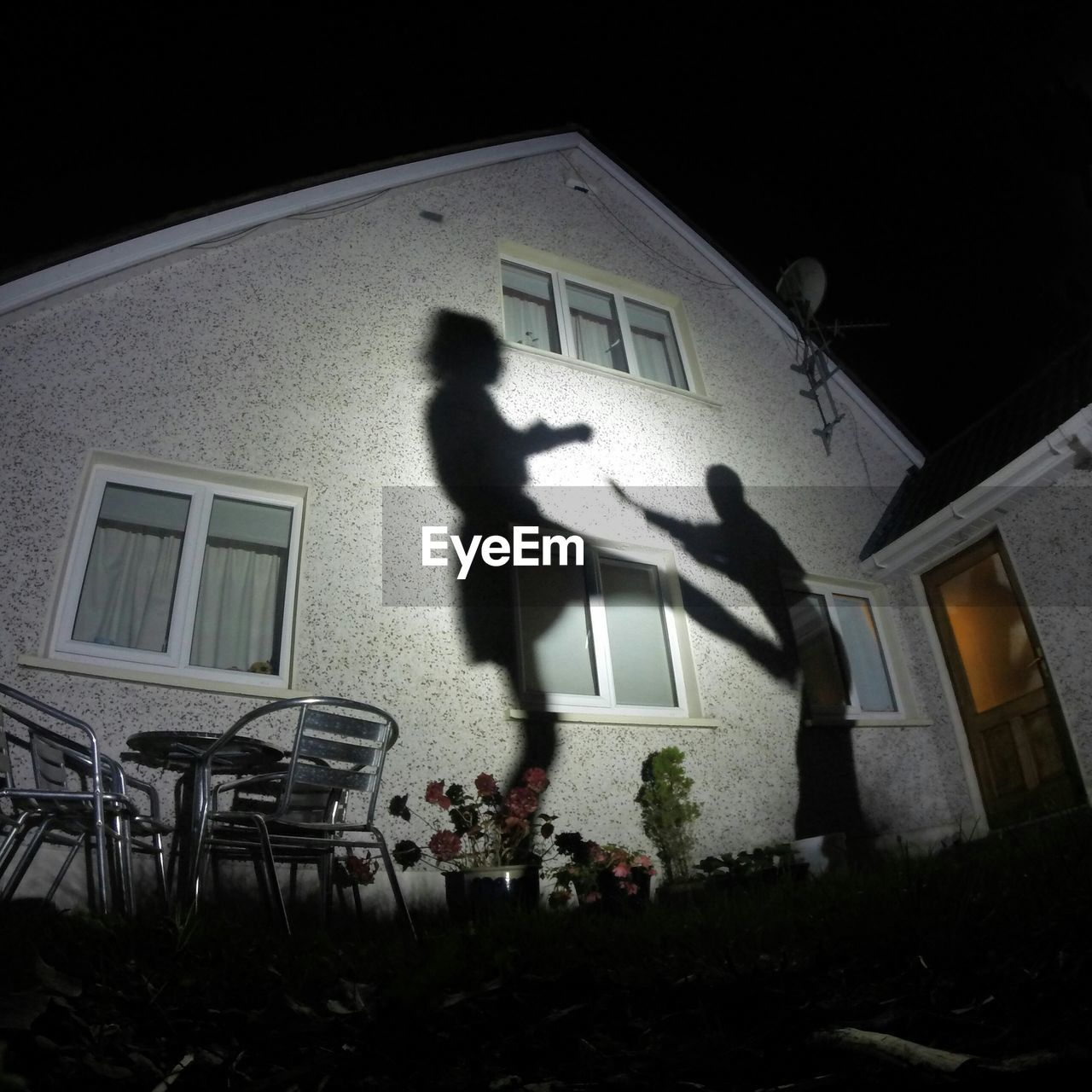 Low Angle View Of Man And Woman Shadow On House