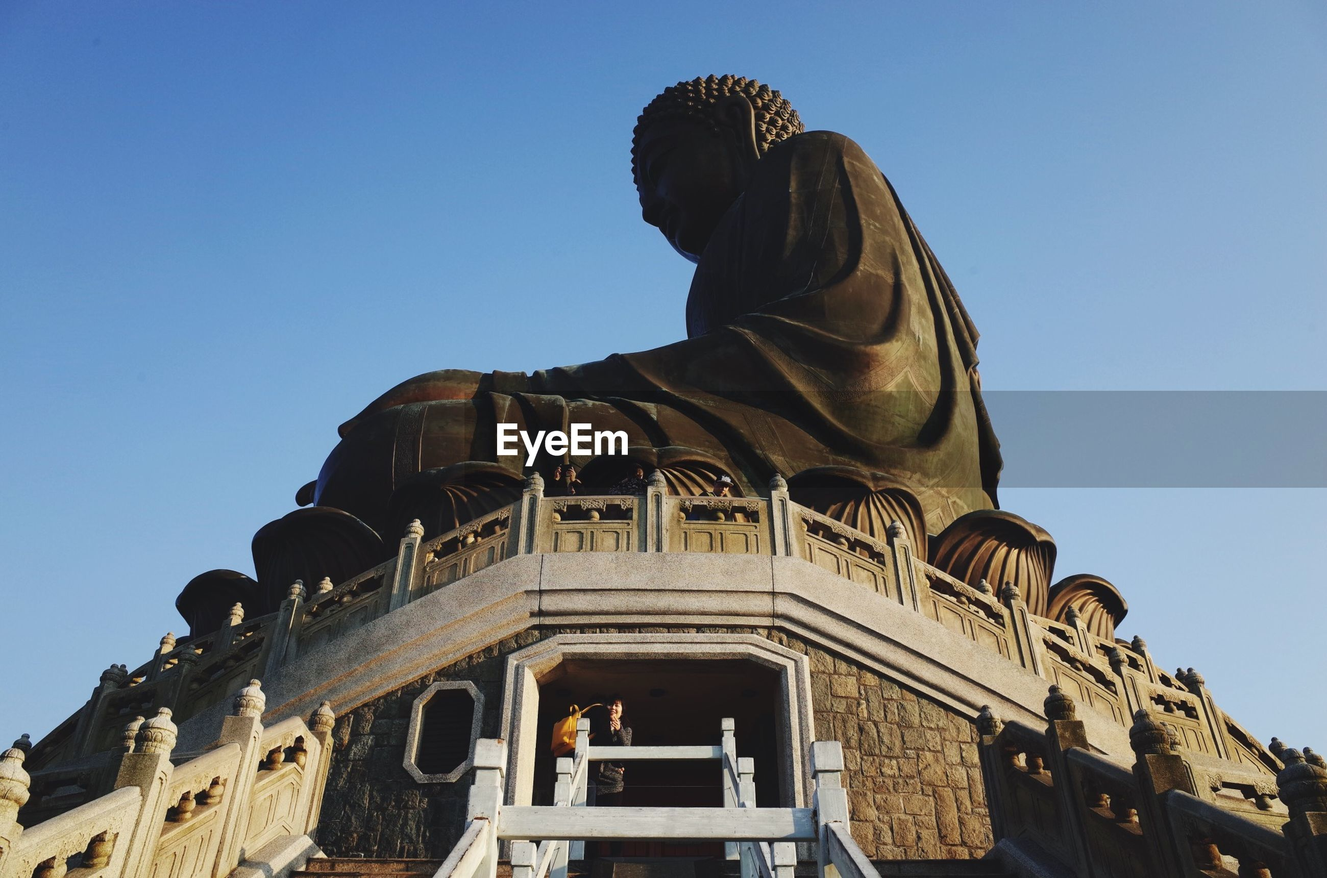 low angle view, clear sky, architecture, building exterior, built structure, statue, sculpture, blue, human representation, art and craft, art, religion, history, creativity, famous place, place of worship, travel destinations, copy space, spirituality