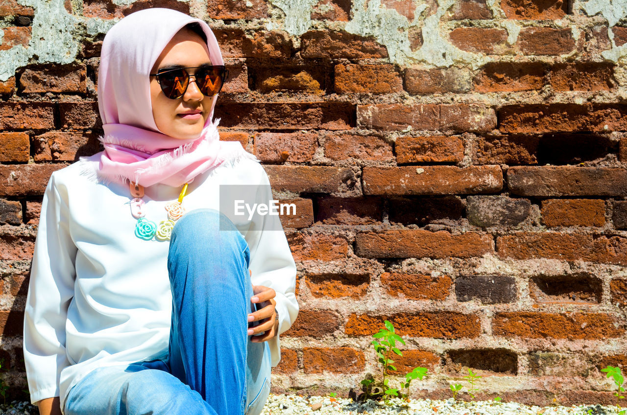 Young Woman Wearing Sunglasses And Scarf Sitting Against Brick Wall On Sunny Day