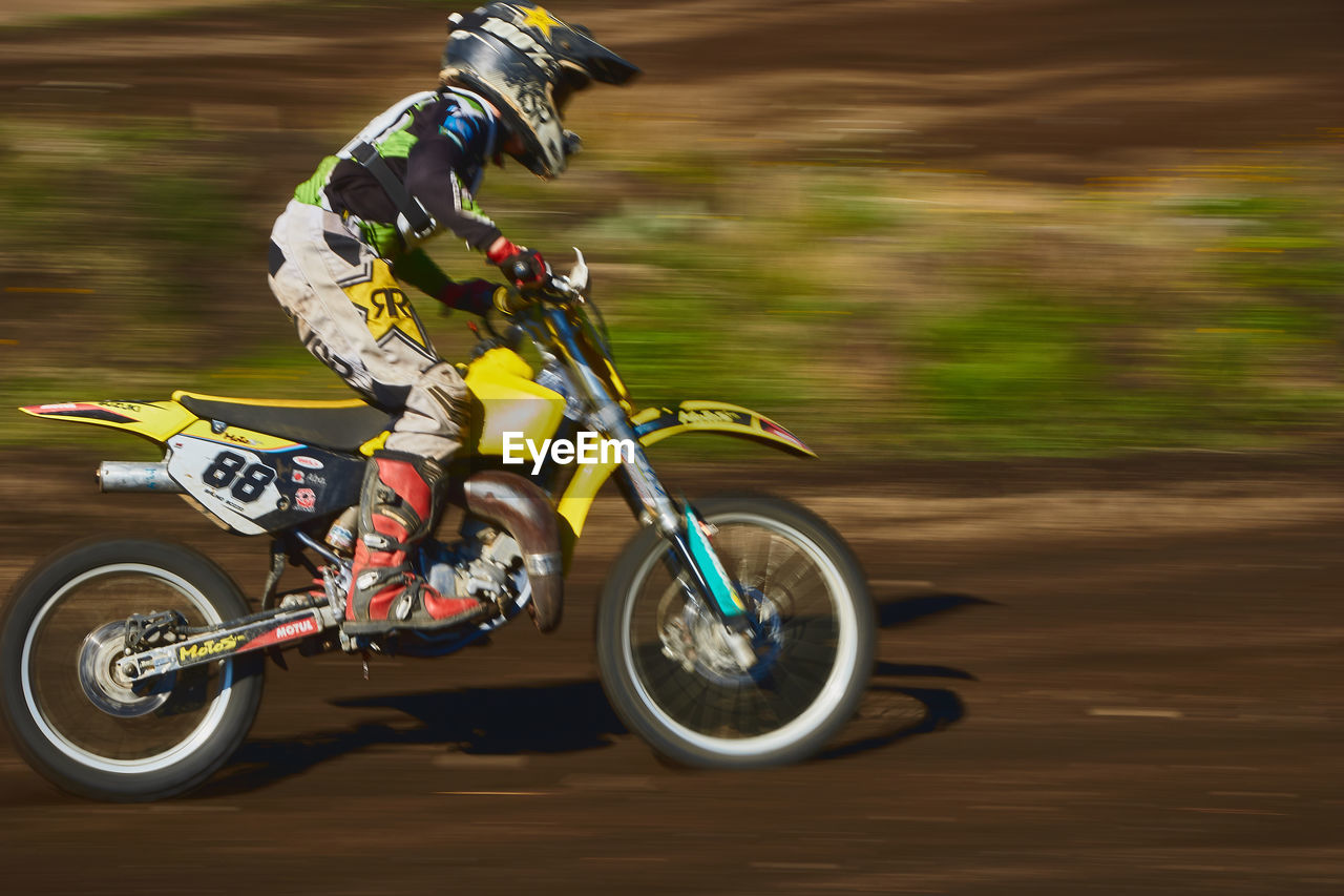 transportation, motion, blurred motion, speed, headwear, mode of transportation, land vehicle, helmet, riding, motorcycle, ride, sport, bicycle, sports helmet, biker, road, one person, day, competition, on the move, outdoors, crash helmet