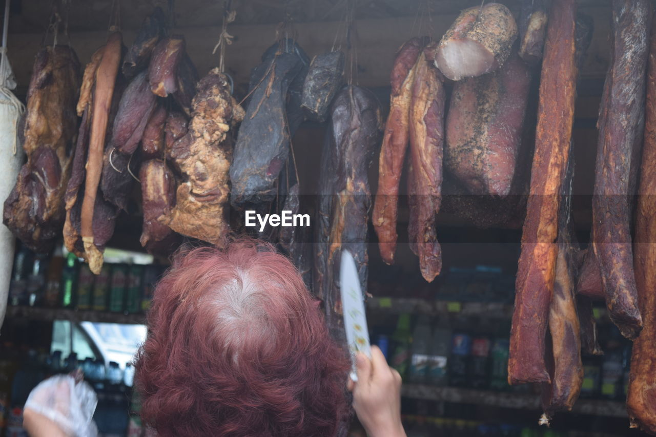 Rear View Of Woman Standing At Butcher Shop