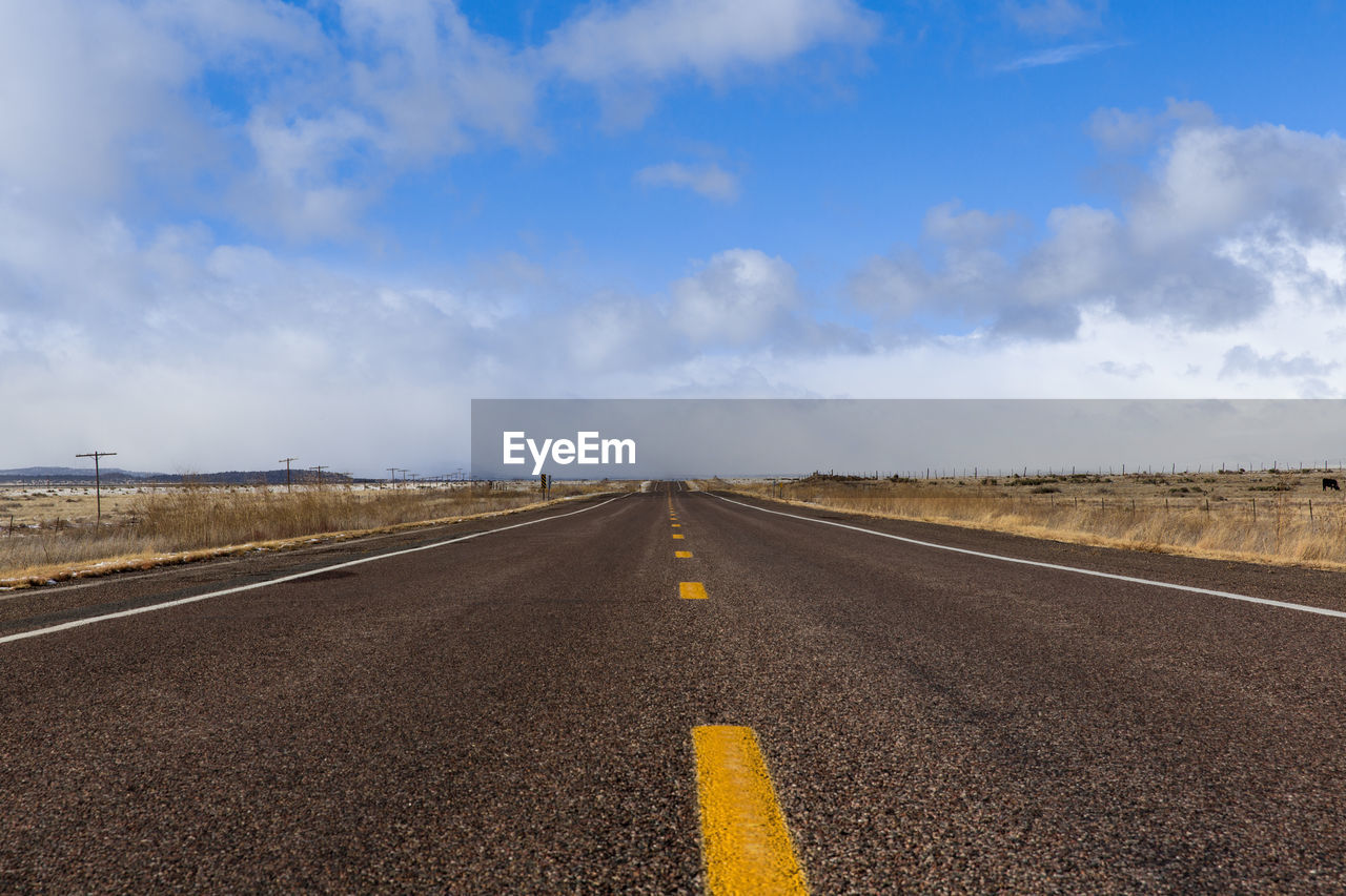 sky, sign, road, direction, cloud - sky, road marking, the way forward, marking, diminishing perspective, symbol, transportation, vanishing point, no people, environment, nature, tranquil scene, land, landscape, day, empty road, outdoors, dividing line